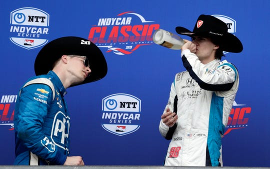 Colton Herta, right, takes a celebratory swig after winning the IndyCar Classic auto race, as second-place finisher Josef Newgarden, left, takes a closer look a the bottle label Sunday, March 24, 2019, in Austin, Texas. Herta, 18, became the youngest winner in IndyCar history after a late-race crash near the entry to pit row helped him steal past the leaders to the checkered flag. (AP Photo/Eric Gay)