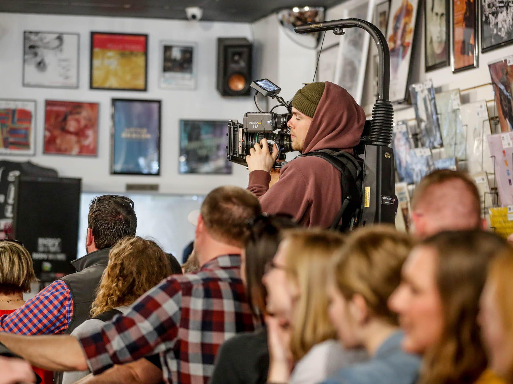 A Mumford & Sons video crew members films as fans pack the store for the the band's special in-store appearance at Indy CD & Vinyl on Monday, March 25, 2019.