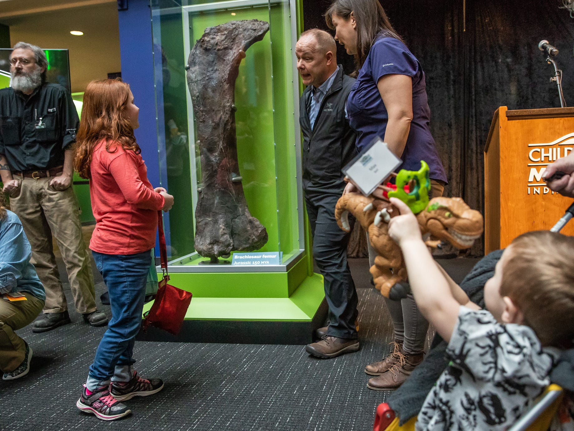 Hailey Bell, 8, (left) talks with Professor Phil Manning (middle), a Children's Museum of Indianapolis scientist-in-residence, and Dr. Victoria Egerton, a Children's Museum of Indianapolis scientist-in-residence, about the newly discovered femur of a Brachiosaur at the Children's Museum of Indianapolis on Monday, March 25, 2019. Bell's brother, Max, was showing off his Tyrannosaurus Rex toy.