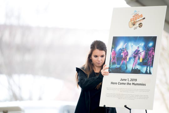 """Savannah Fielder, events and media planner with Second Harvest Food Bank, puts up a poster of the June 1 """"Here Come the Mummies"""" concert during a Music Feeds summer concert series lineup announcement at the Tennessee Amphitheater in World's Fair Park in Knoxville, Tennessee on Monday, March 25, 2019. Proceeds from the concert series will go to benefit Second Harvest Food Bank."""