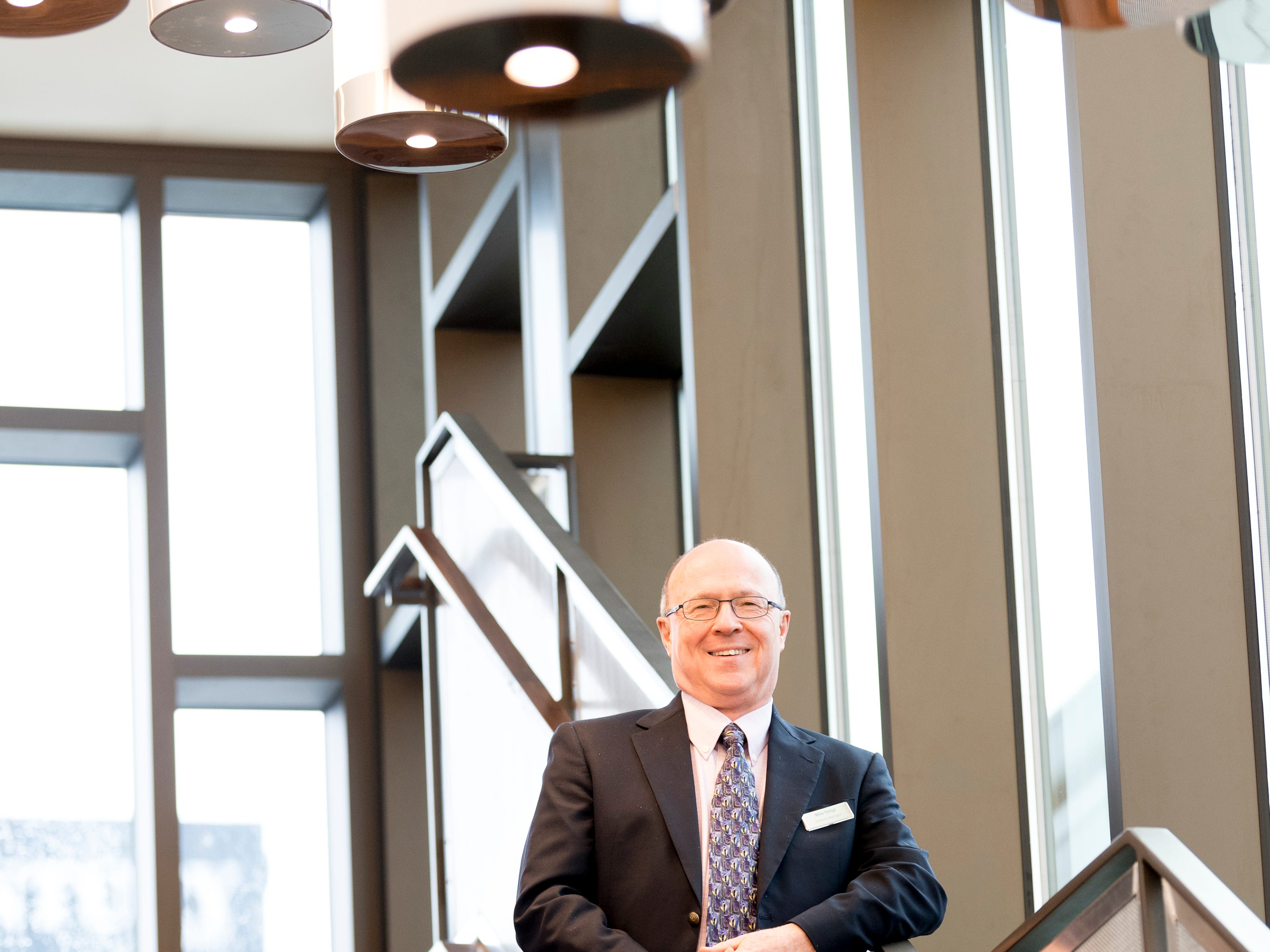 General Manager Mike Sellge poses for a photo March 25, 2019, on the grand staircase at the new Courtyard and Residence Inn by Marriott at 210 Church Ave. in Knoxville. The hotel is the first of its kind in Knoxville to offer two different tiers of hospitality within the same building.