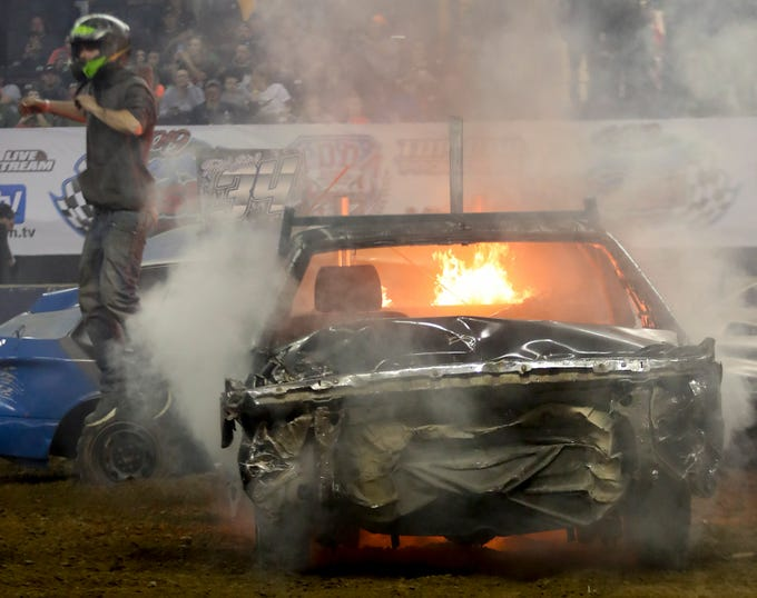 Tim Haniszewski jumps from his car as it goes up in flames at the 4th annual Bluegrass Bash Demolition Derby in Freedom Hall on March 23.