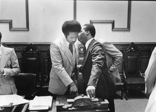 Shelby Lanier Jr., left, talks with Renault Robinson, information officer of the National Black Police Association, during a break in Lanier's hearing before the Civil Service Board in City Hall aldermanic chambers. Aug. 8, 1977.