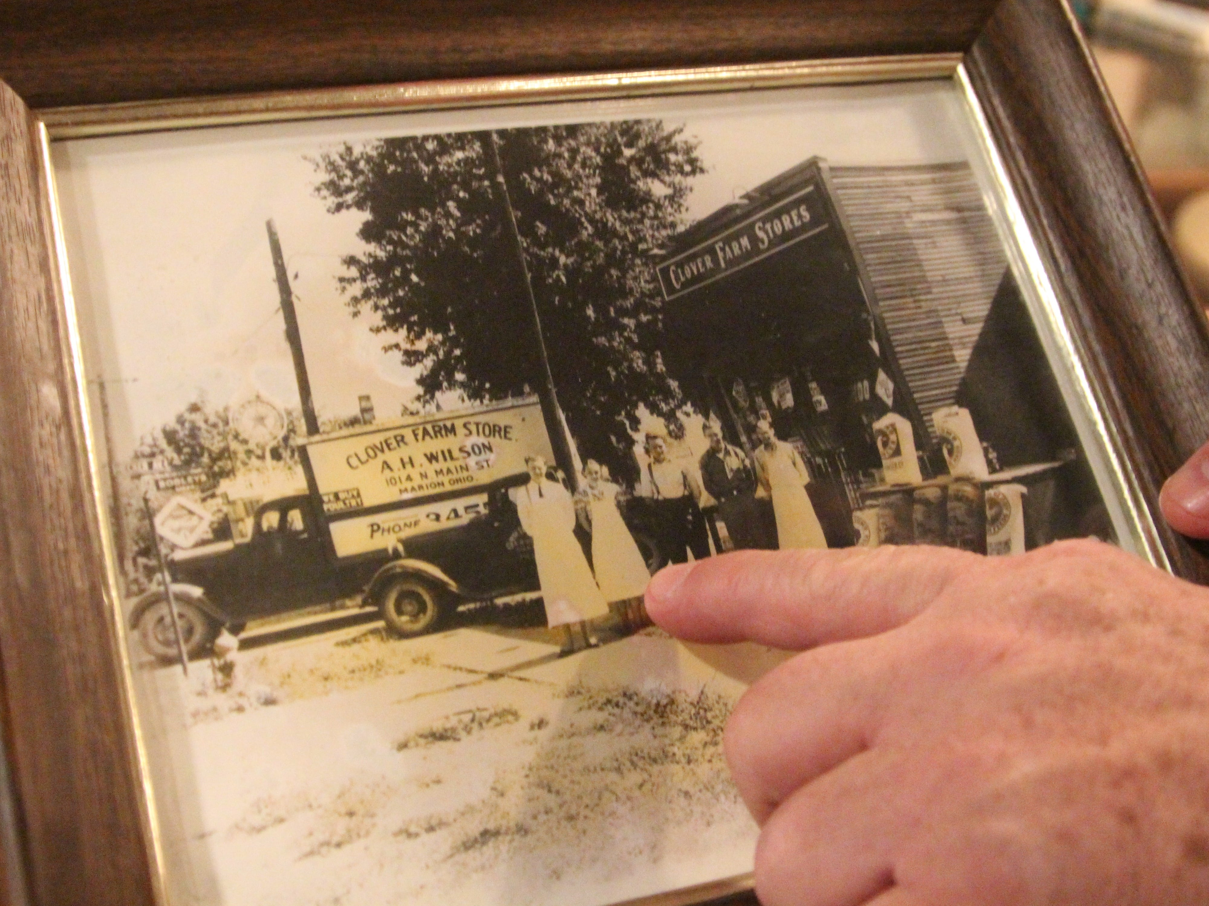 Mike Wilson points to a picture of his great uncle Alfred Harvey Wilson who helped manage the Clover Farm Stores in northern Ohio.