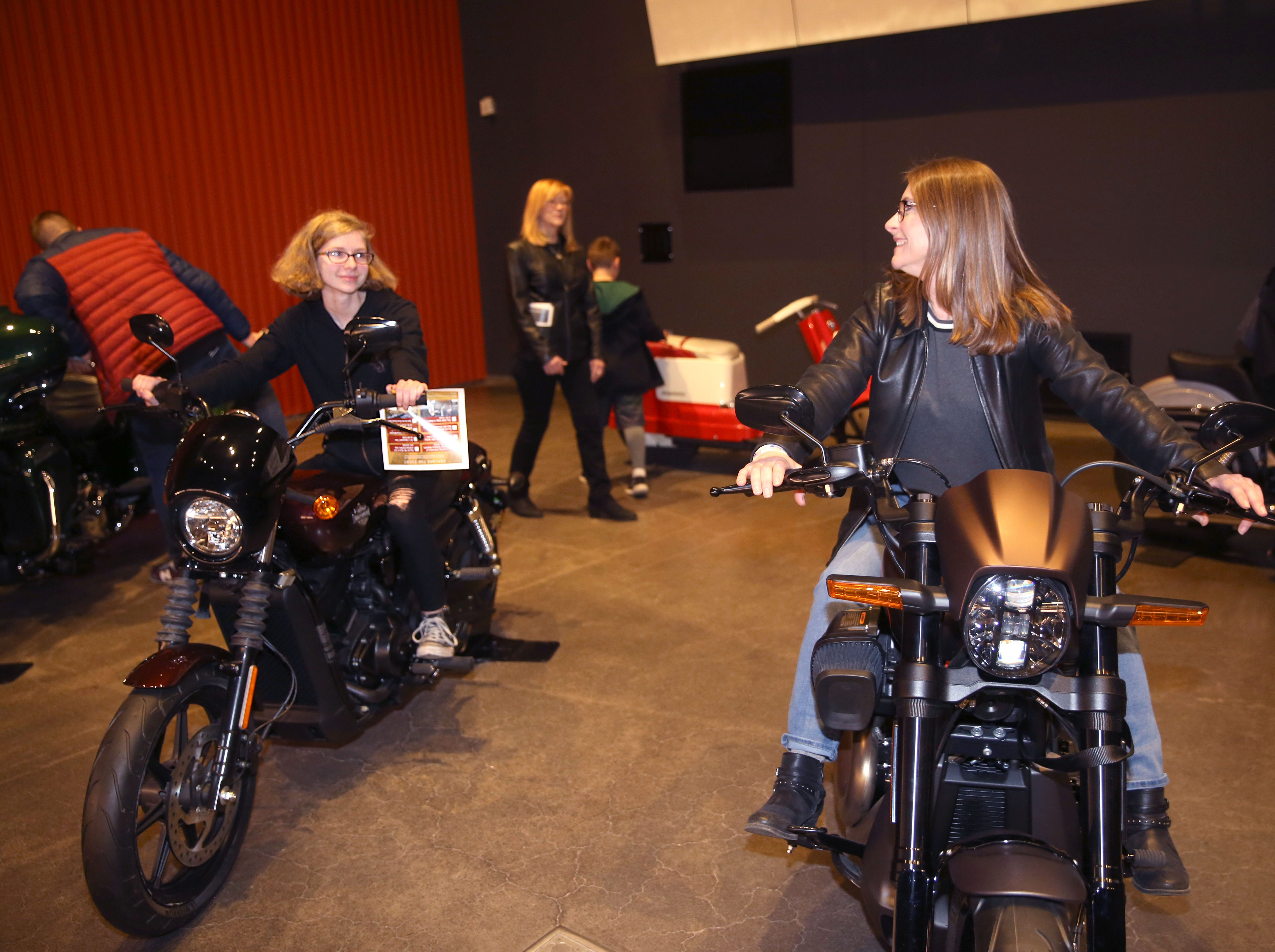 Secret Symphony concertgoers Alexandra Robertson (left) and her mother Robin Robertson try out motorcycles before the Milwaukee Symphony's performance at the Harley-Davidson Museum Sunday.