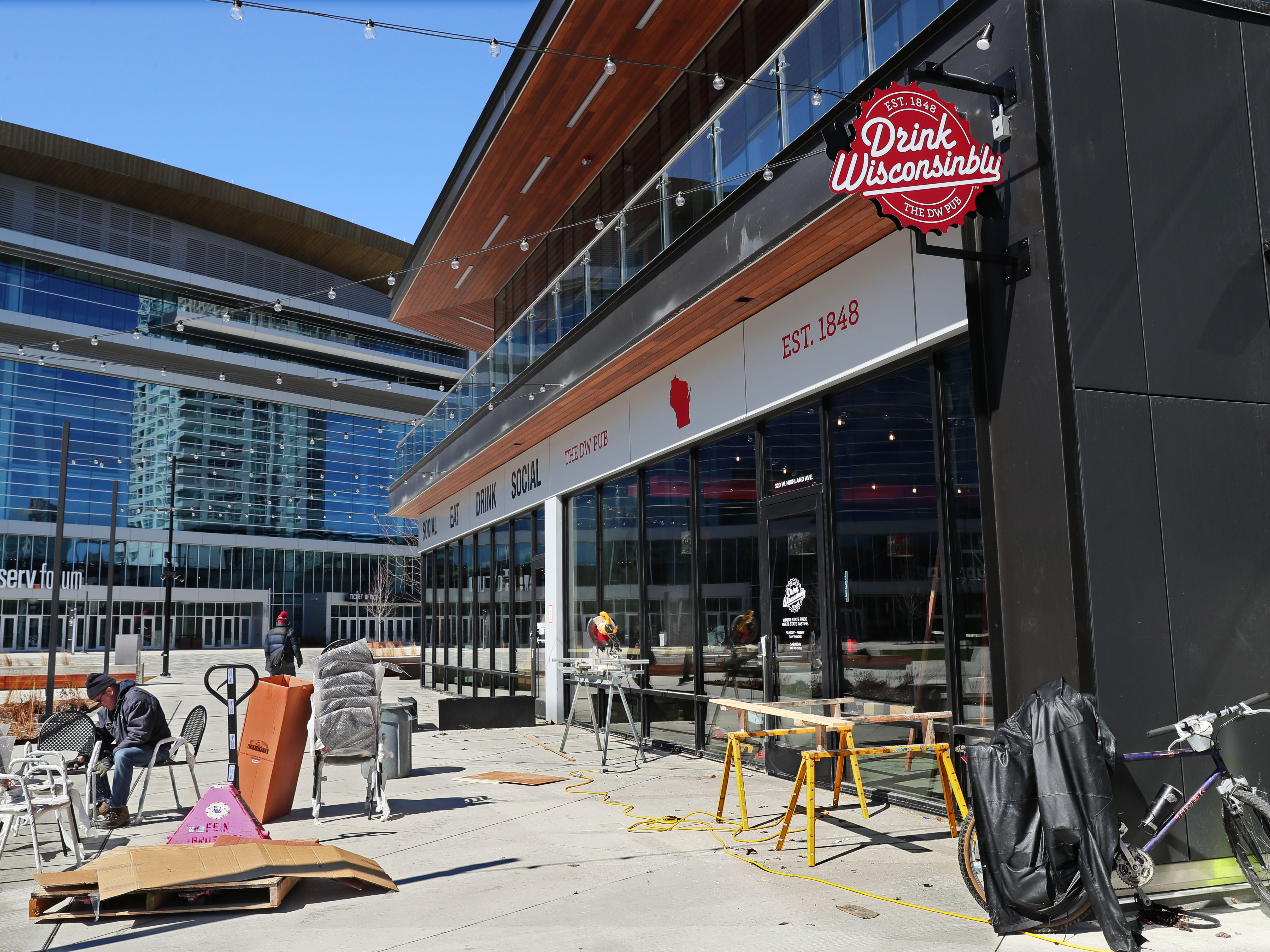 Workers unwrap chairs on the patio in front of the new Drink Wisconsinbly Pub. The bar is making final preparations for opening.