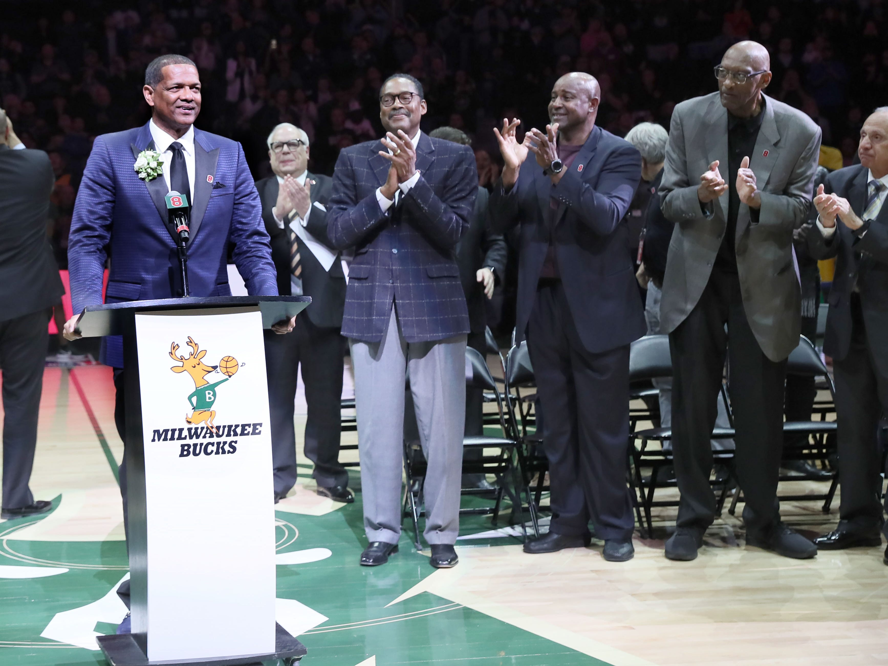 Marques Johnson (left) takes the dais during a halftime ceremony Sunday at Fiserv Forum that saw his number retired by the Bucks as Jim Paschke (from left) and former teammates Junior Bridgeman, Sidney Moncrief and Bob Lanier applaud.