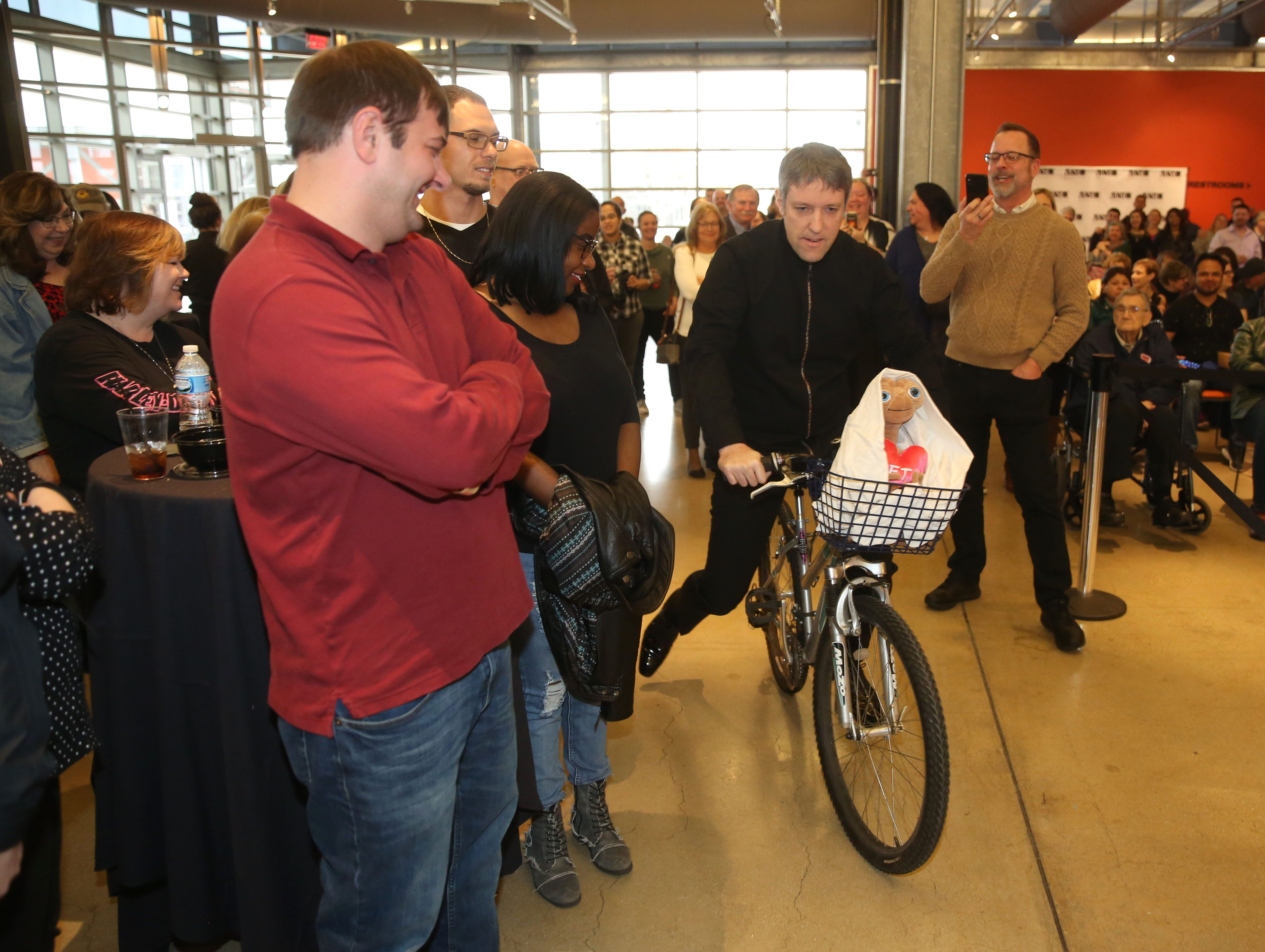 """After starting the musicians playing music from the movie """"ET,"""" associate conductor Yaniv Dinur re-enacts his trip to the Milwaukee Symphony's Secret Symphony performance Sunday at the Harley-Davidson Museum."""