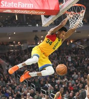 Giannis Antetokounmpo of the Bucks hangs on the rim after throwing down a dunk against the Cavaliers on Sunday.