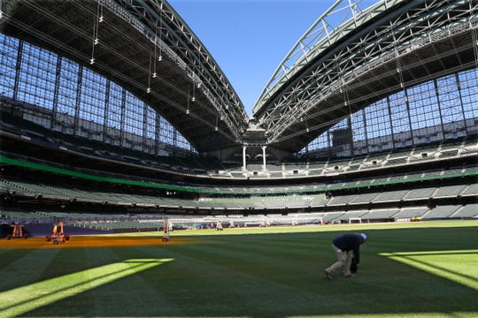 A member of the Brewers grounds crew is searching for and filling low spots on the field.