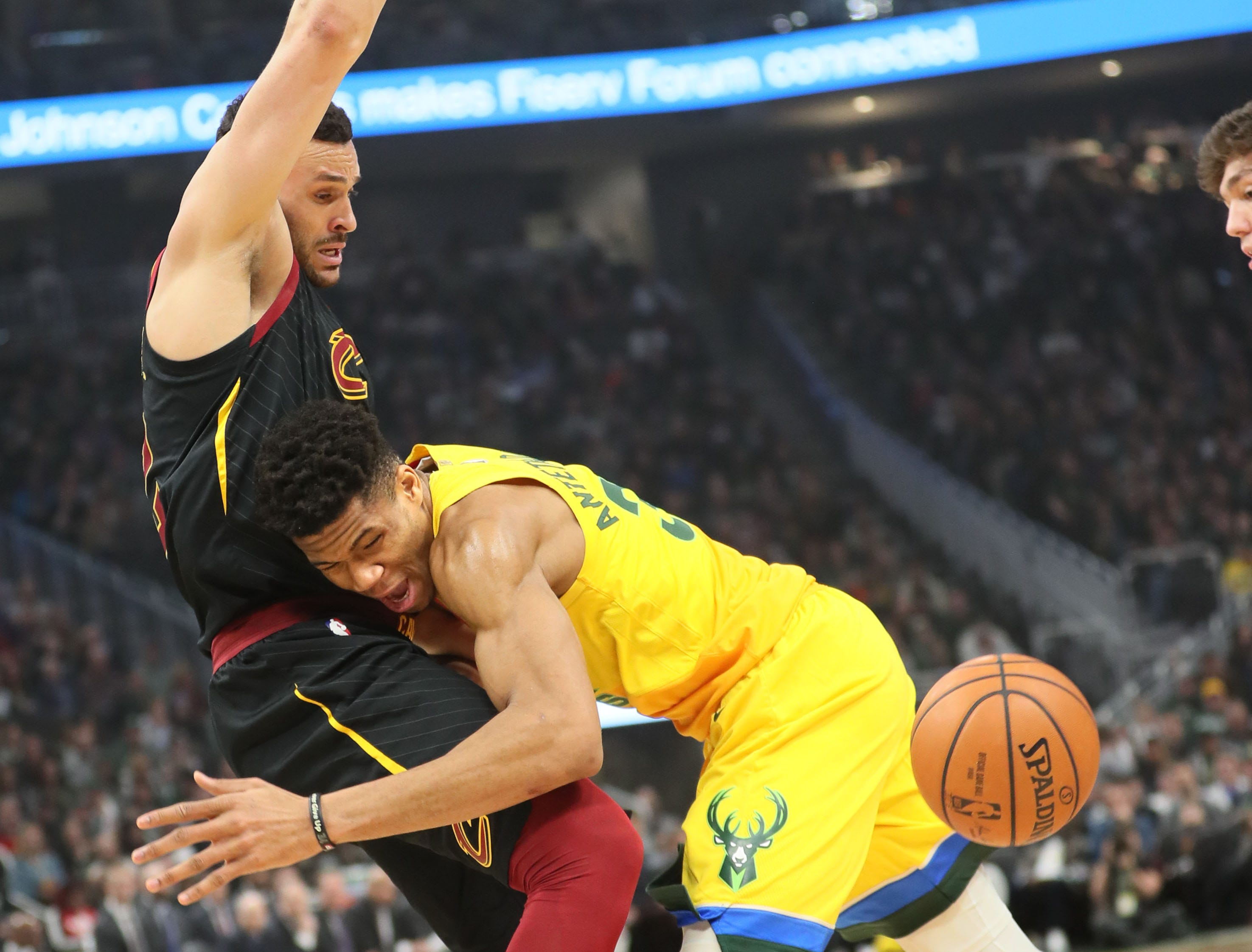 Giannis Antetokounmpo of the Bucks loses control of the ball after running into the Cavaliers' Larry Nance Jr. on Sunday.