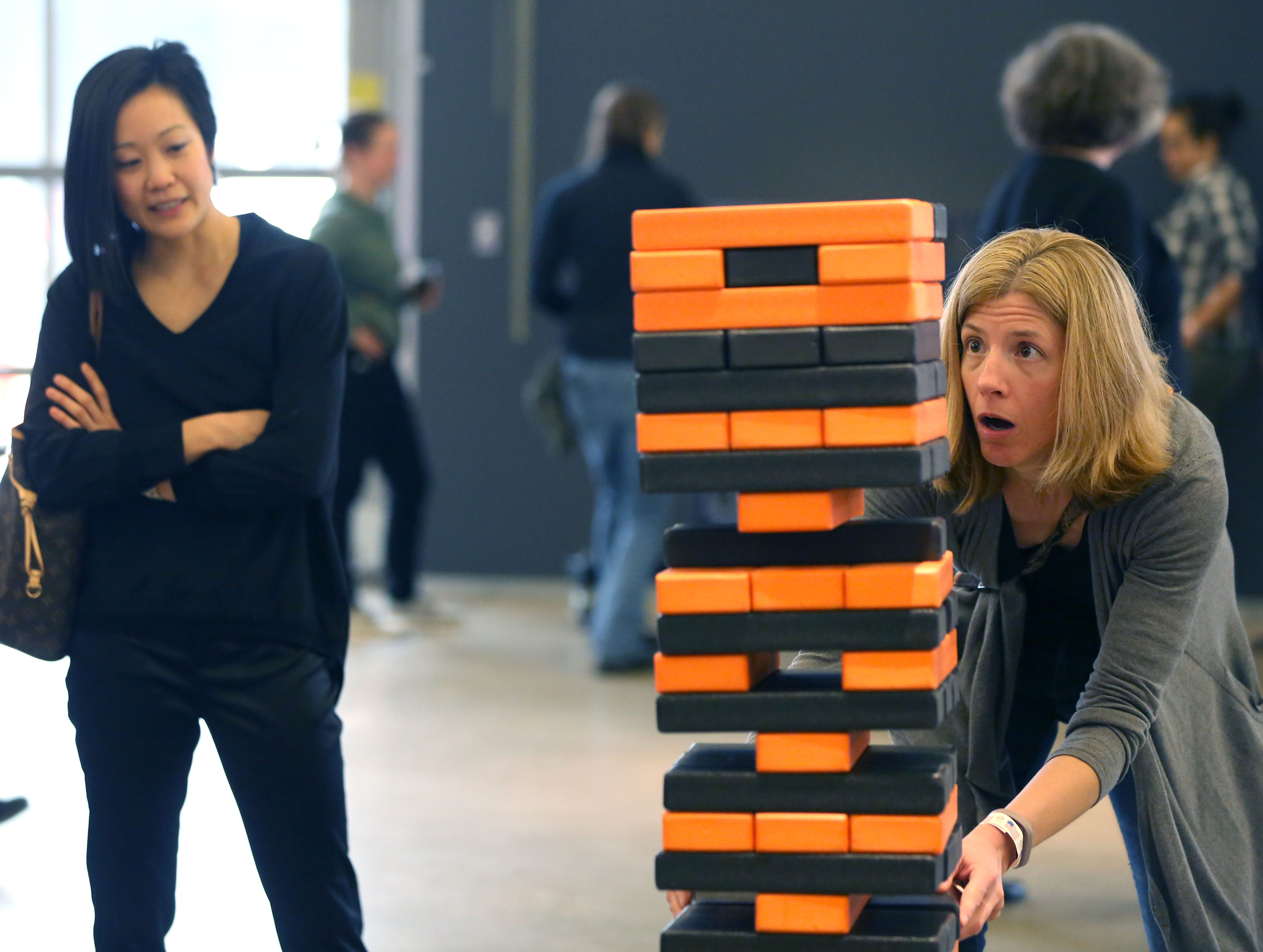 Concertgoer Dee Leung (left_ watches her friend Jill Kortebein play the Harley-Davidson version of Jenga before the Milwaukee Symphony's Secret Symphony performance at the Harley-Davidson Museum Sunday.