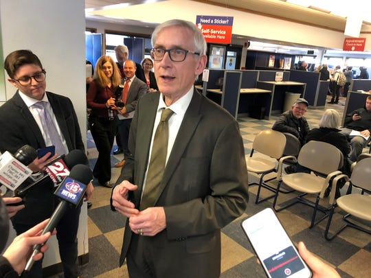 Gov. Tony Evers visits a Department of Motor Vehicles office in Madison. Evers tells reporters he will move as quickly as possible to fill the 82 appointed positions he just vacated. Evers also said he has no immediate plans to replace Wisconsin Economic Development Corp. CEO Mark Hogan.