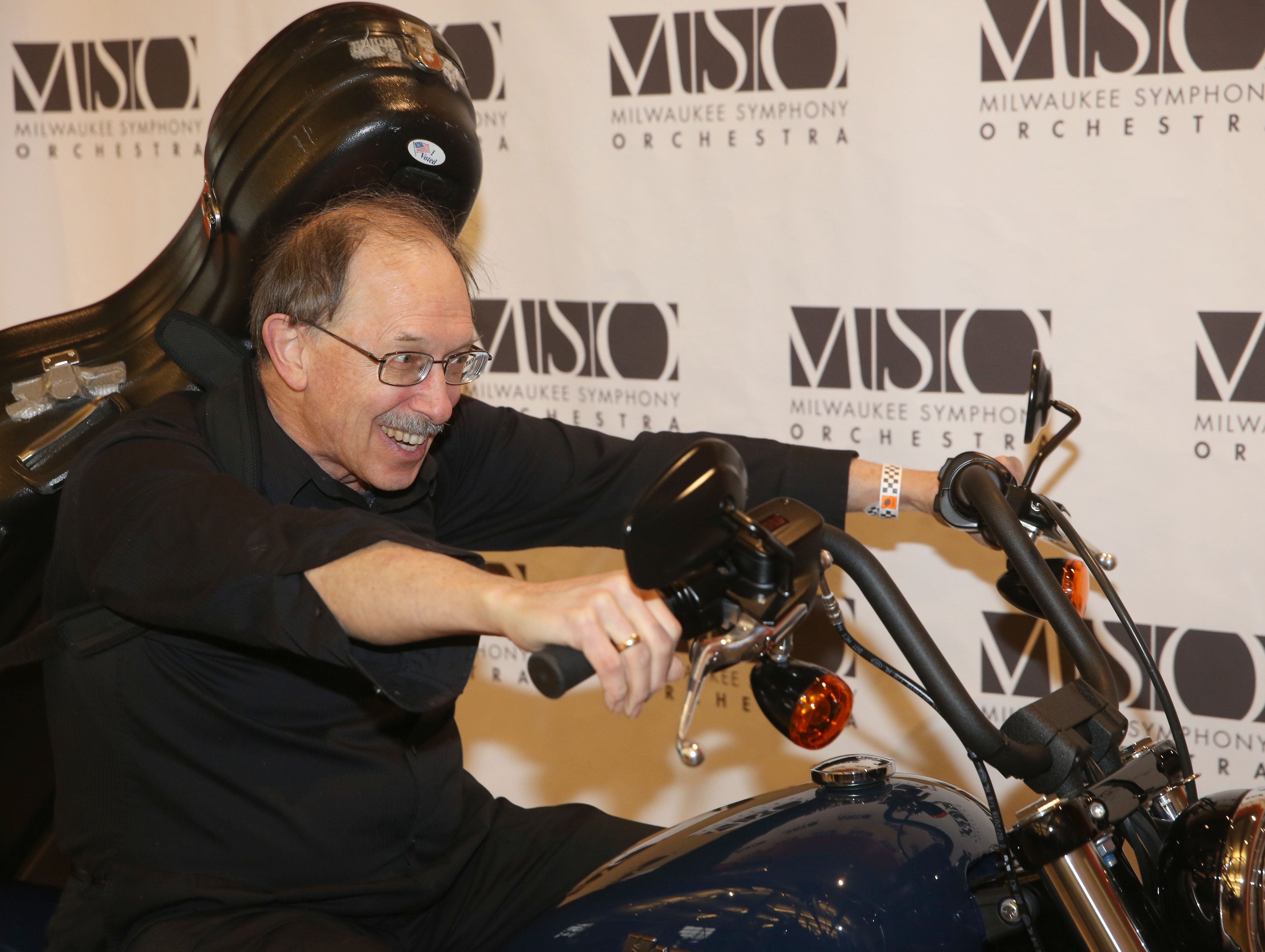 Cellist Gregory Matthews poses on a motorcycle before the Milwaukee Symphony's Secret Symphony performance at the Harley-Davidson Museum Sunday.
