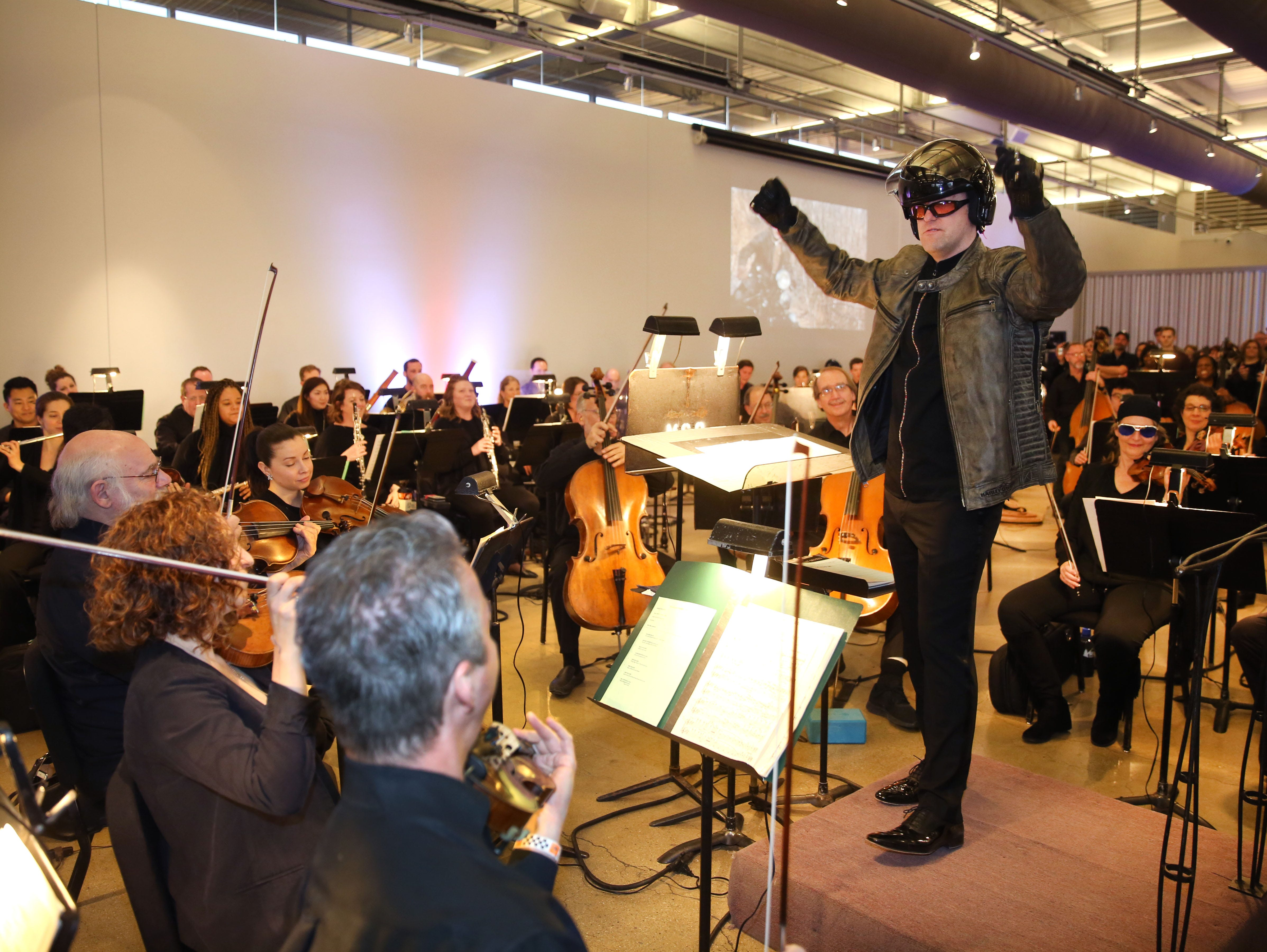 Decked out in gear, Yaniv Dinur conducts the Milwaukee Symphony during a Secret Symphony performance Sunday at the Harley-Davidson Museum.