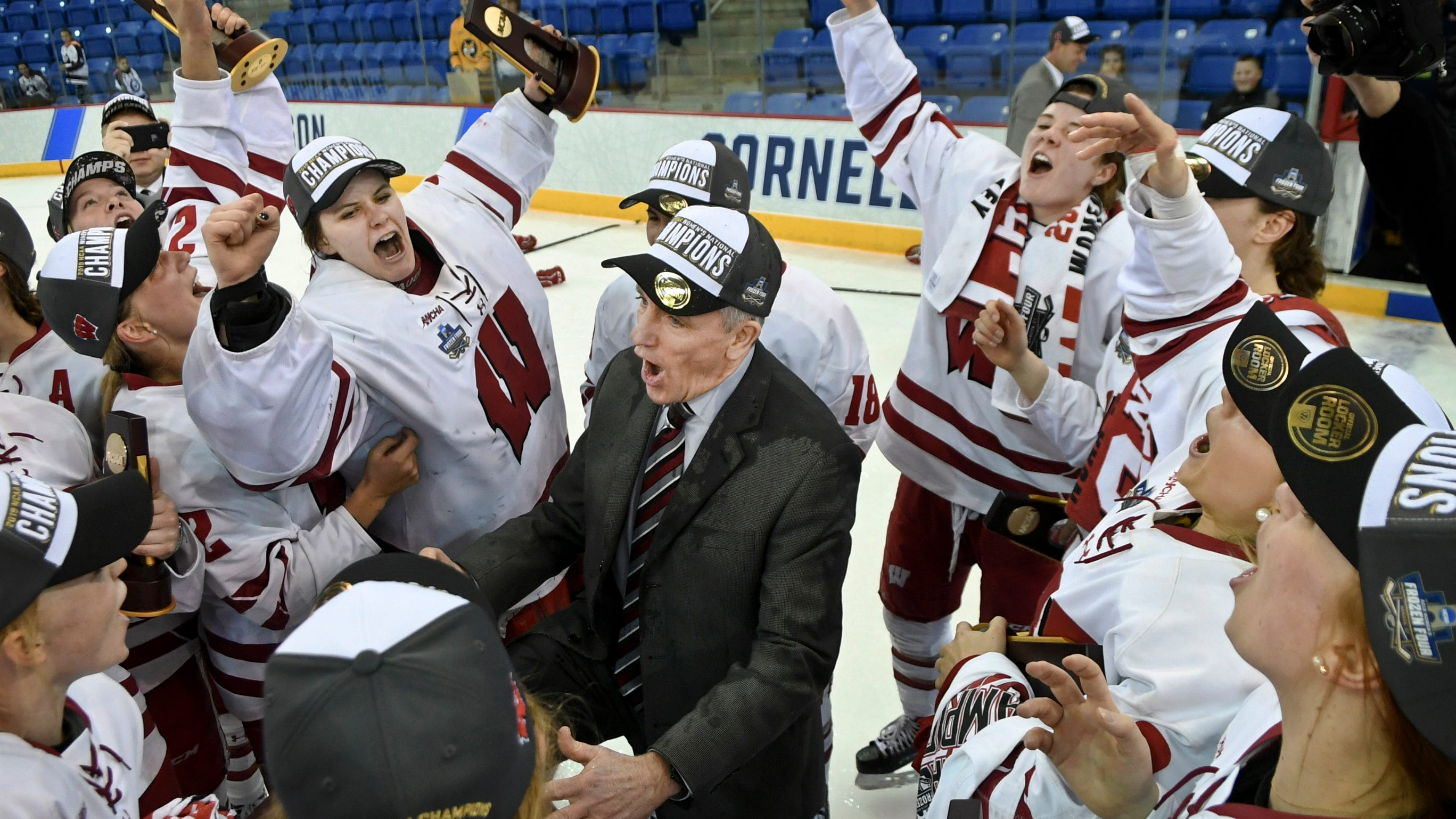 Wisconsin coach Mark Johnson is surrounded by his team as they celebrate after defeating Minnesota 2-0 for the NCAA Division I women's Frozen Four hockey championship Sunday, March 24, 2019, in Hamden, Conn. (AP Photo/Stephen Dunn) ORG XMIT: CTSD112