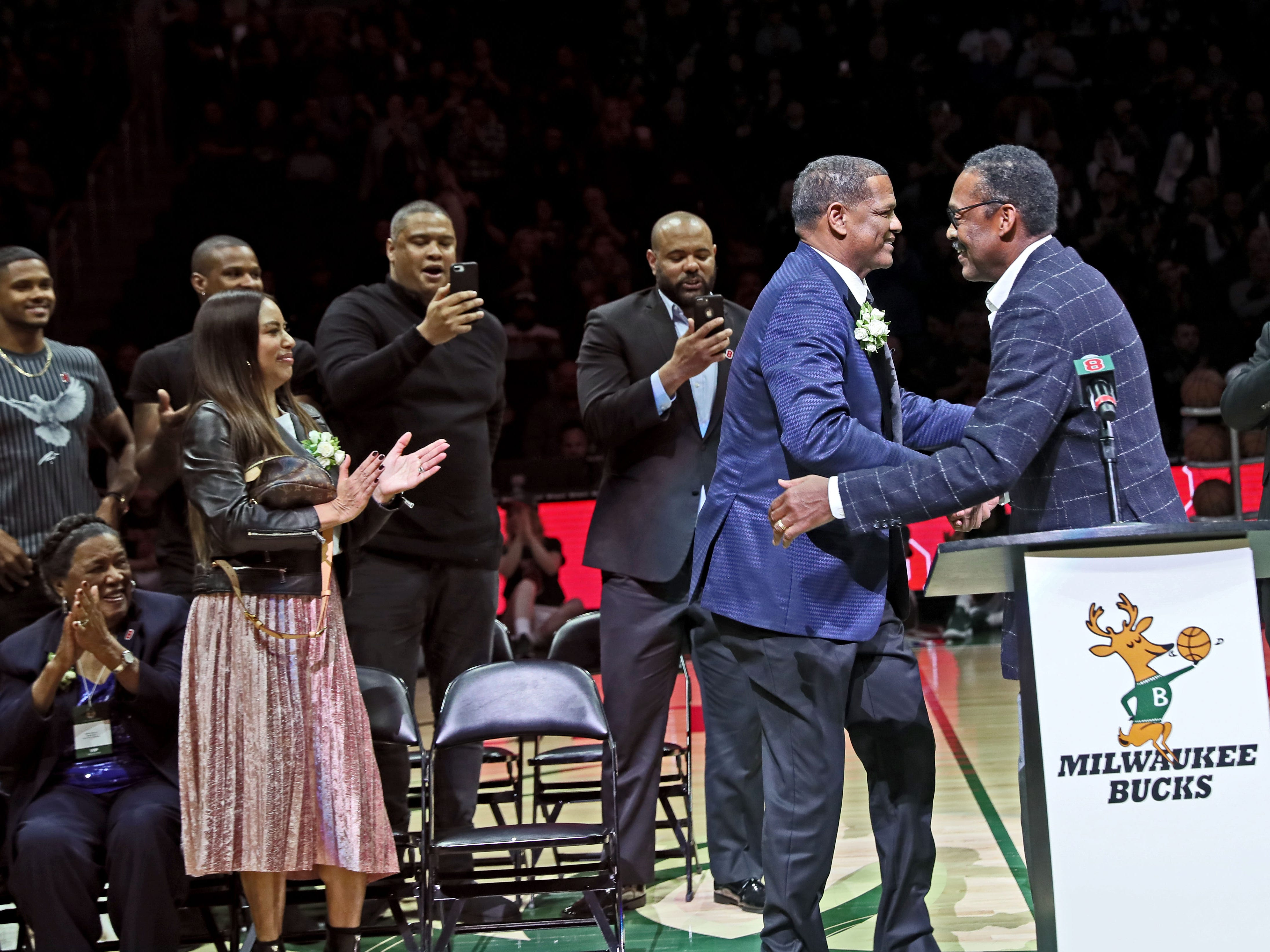 Junior Bridgeman (right) congratulates Marcus Johnson during a halftime ceremony in which the Bucks retired Johnson's No. 8 jersey.