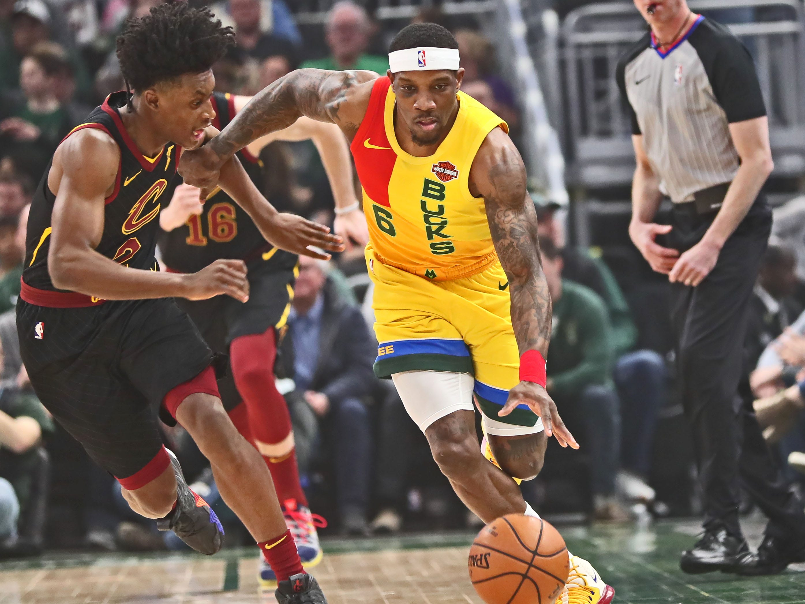 Bucks guard Eric Bledsoe barely stays in bounds as he brings the ball up the court against the Cavaliers' Collin Sexton on Sunday.