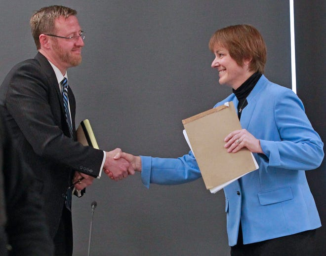 Wisconsin Supreme Court candidates Judge Brian Hagedorn, left, and Judge Lisa Neubauer shake hands following their forum at the Milwaukee Bar Association on March 19.