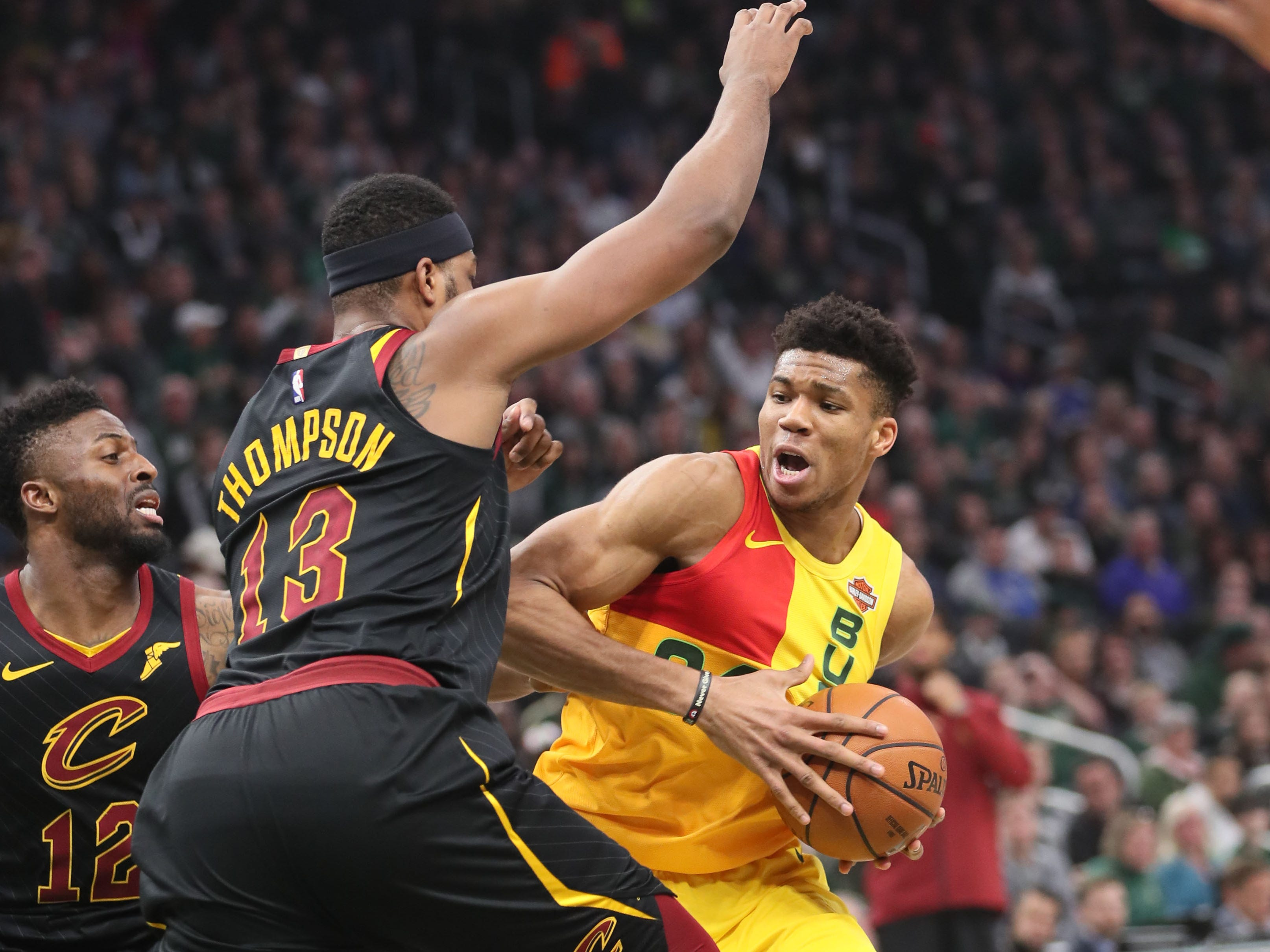 Giannis Antetokounmpo of the Bucks drives on the Cavaliers' Tristan Thompson in the paint Sunday.