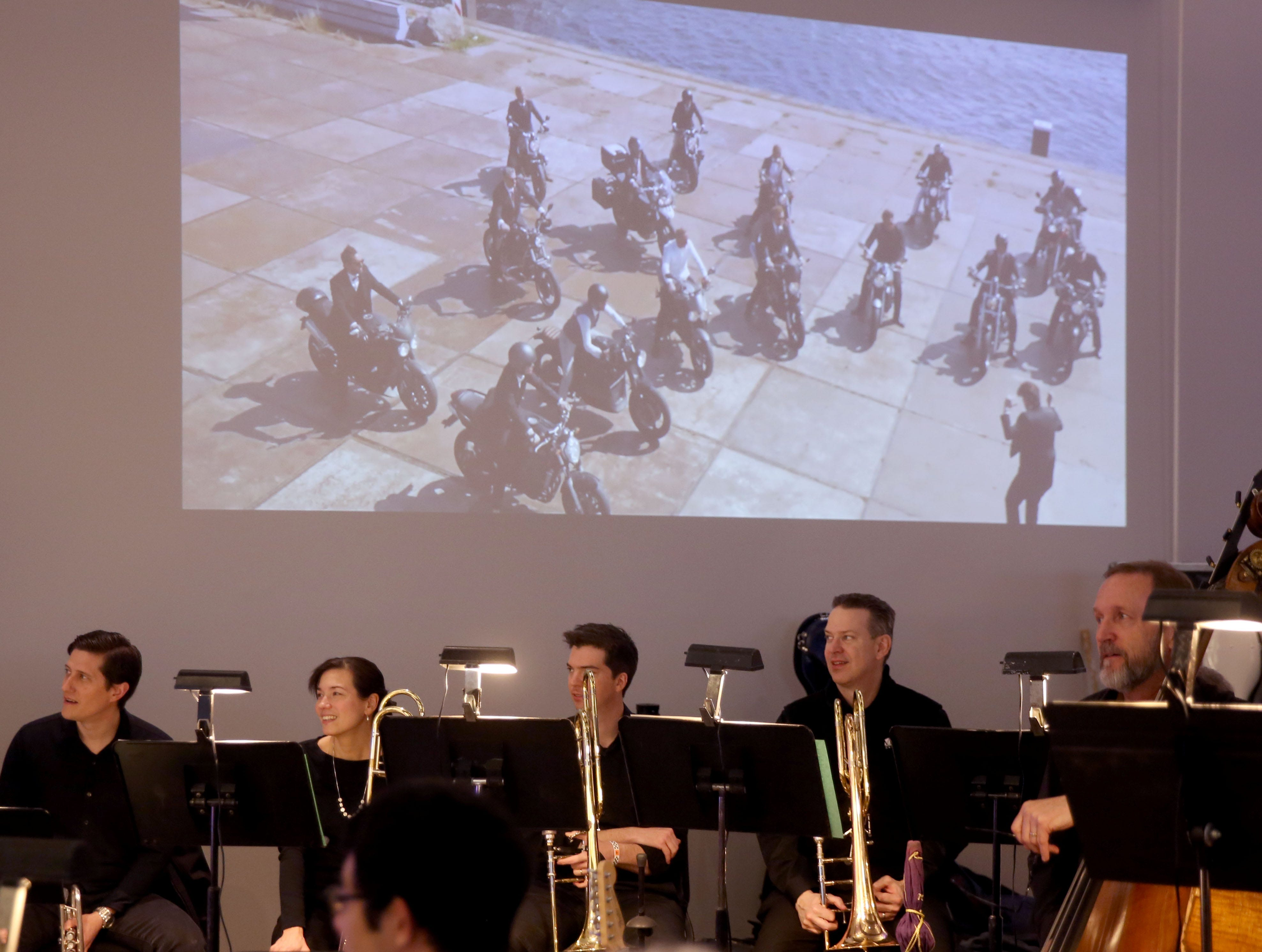 Members of the Milwaukee Symphony watch an introduction video before the orchestra's Secret Symphony performance at the Harley-Davidson Museum Sunday.