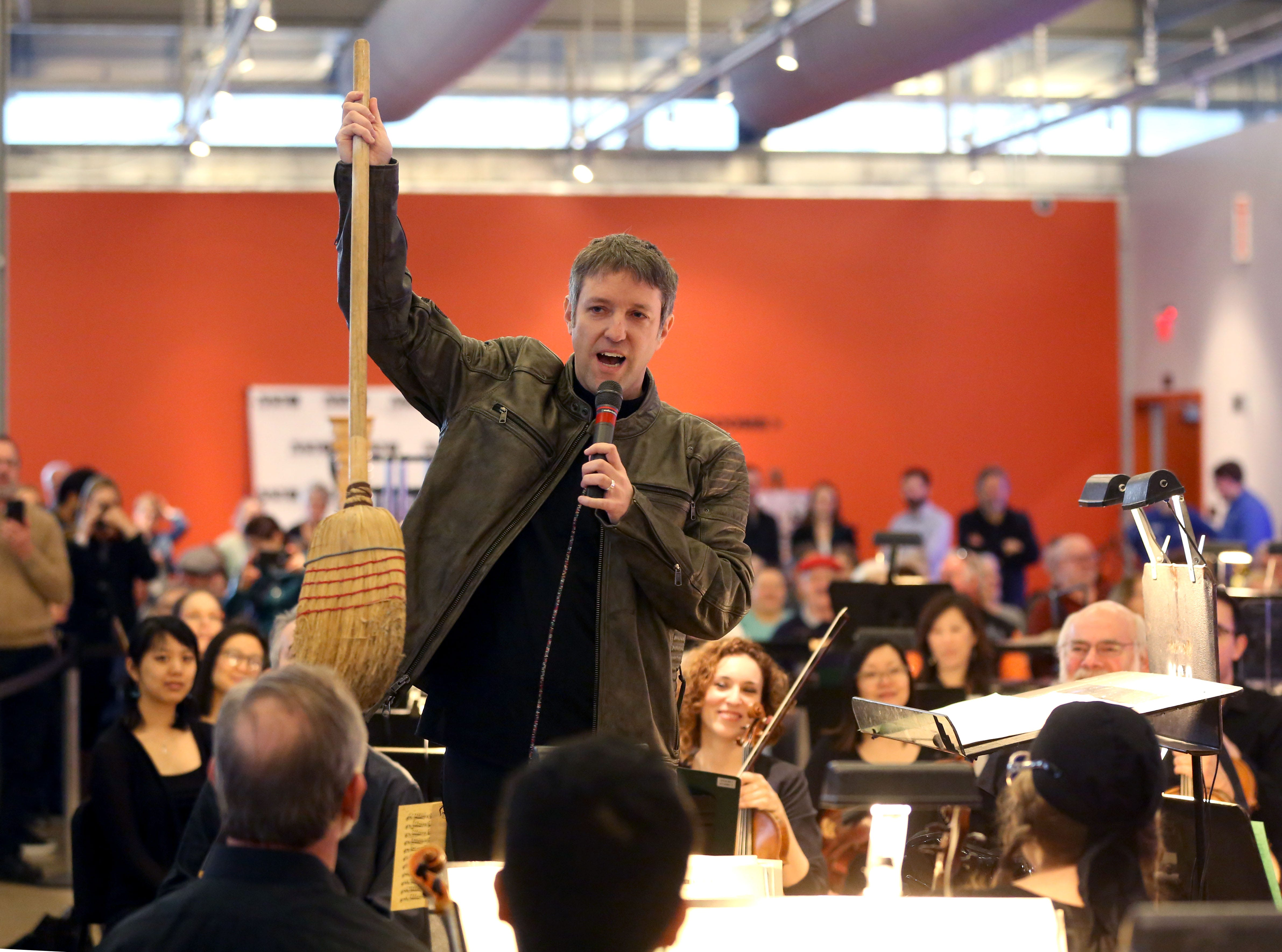 """Conductor Yaniv Dinur playfully displays the """"first Harley-Davidson bike"""" during the Milwaukee Symphony's Secret Symphony performance Sunday at the Harley-Davidson Museum."""