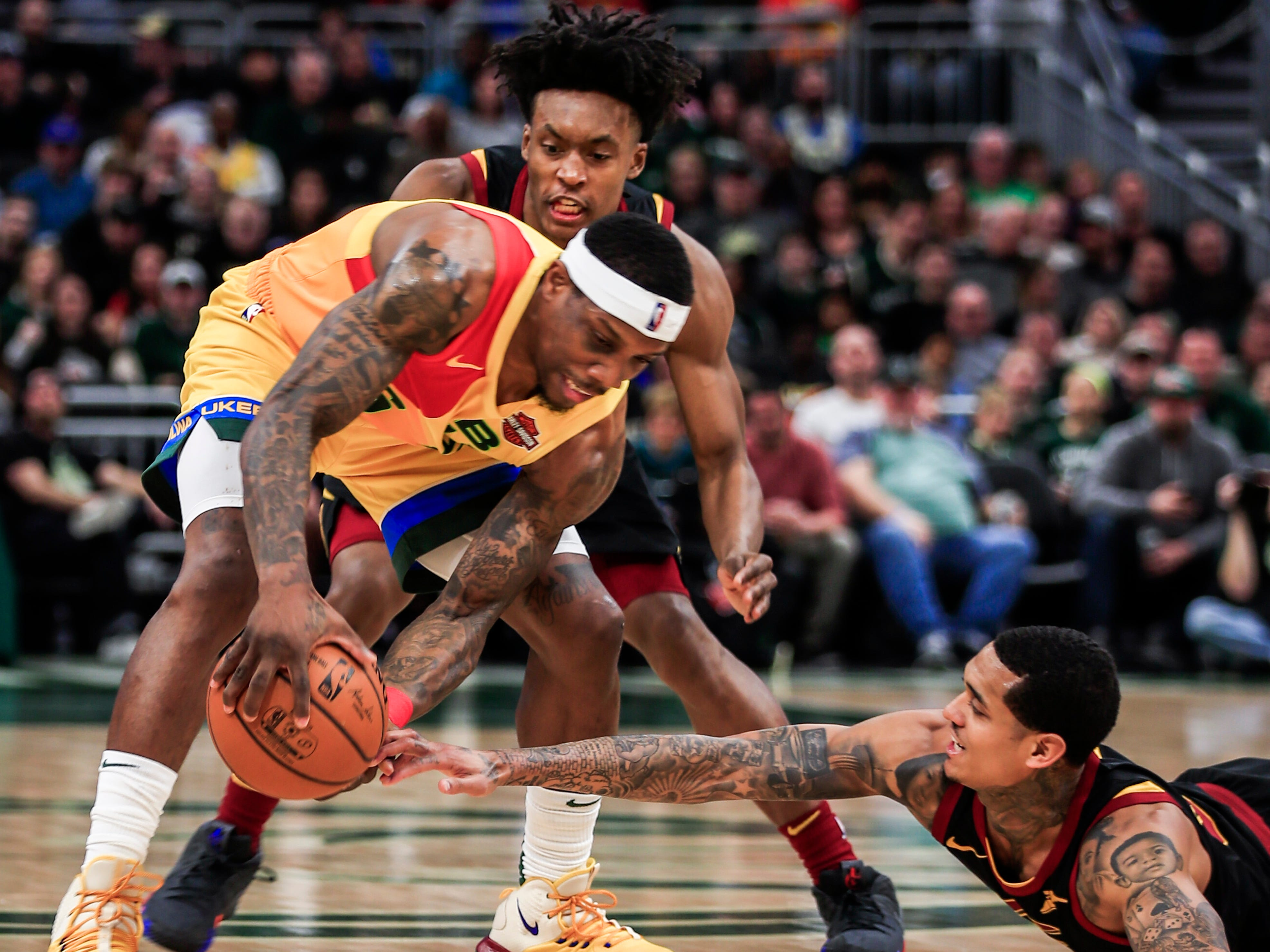 Bucks guard Eric Bledsoe grabs a loose ball before either Jordan Clarkson (right) or Collin Sexton of the Cavs can get to it.