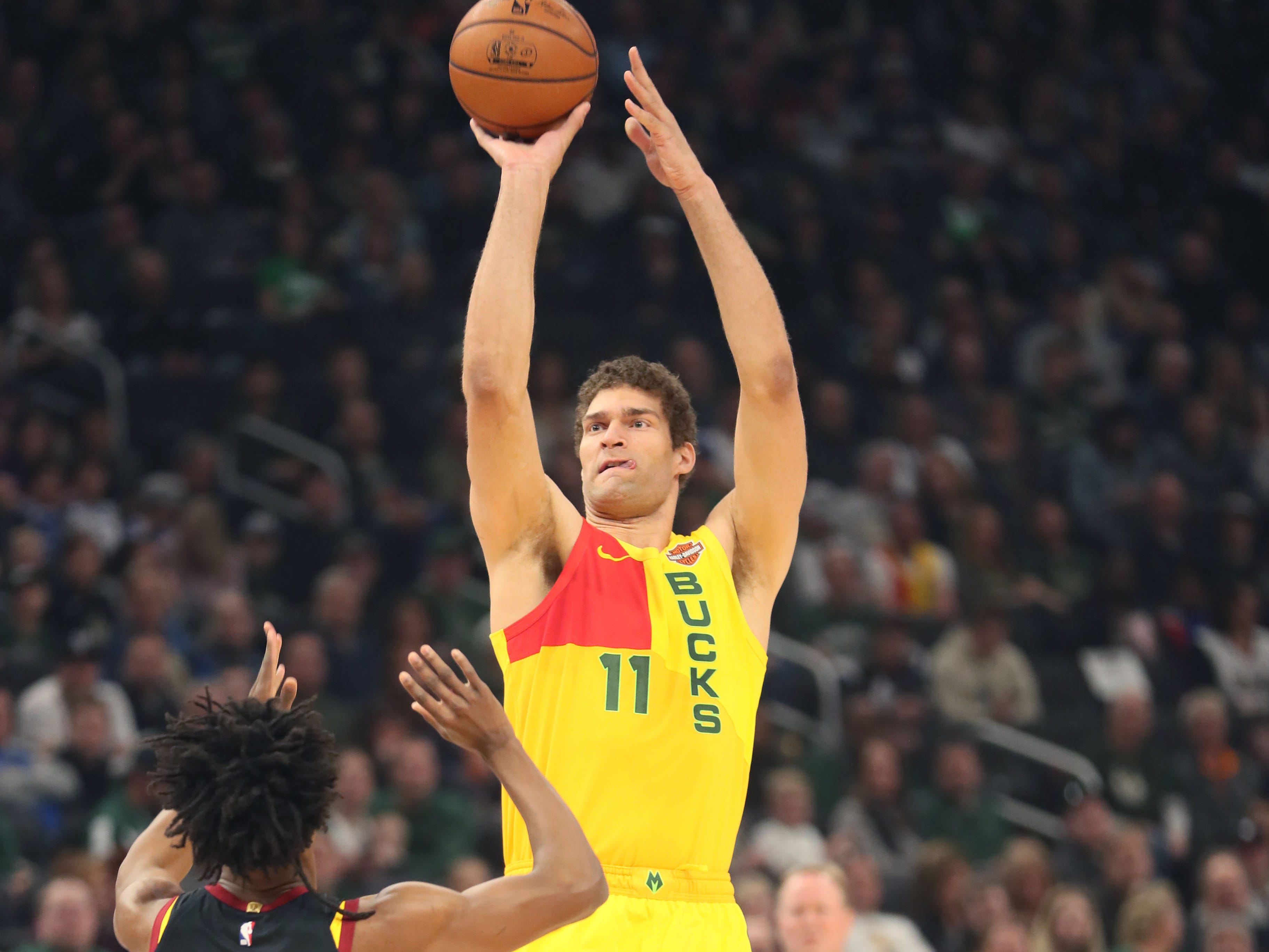 Bucks center Brook Lopez launches a three-pointer in front of the Cavaliers' Collin Sexton on Sunday afternoon.