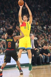 Bucks center Brook Lopez launches a three-pointer in front of the Cavaliers' Collin Sexton on March 24.