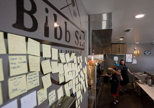 Notes mark pre-paid slices at Bibb St. Pizza in Montgomery, Ala., on Monday, March 25, 2019. Customers can pay for an extra slice and leave a note for someone in need to redeem later.