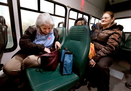 Mindy Hughes looks through her purse for her phone as she rides the Rover bus to work Tuesday, March 19, 2019. It costs $1 to ride Rover, which fits into Hughes' budget plan. But on Saturday she must pay for a ride to work, which costs around $11.