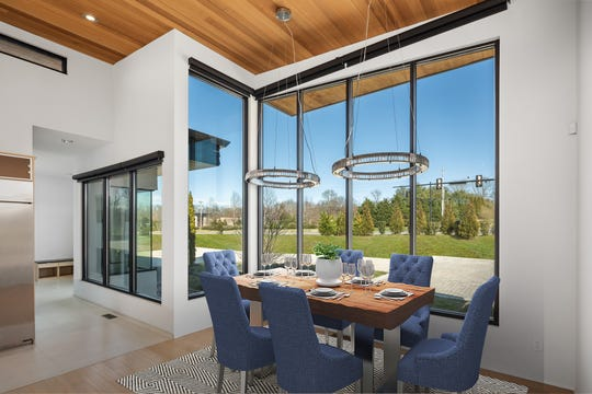 The home's dining room also takes advantage of large windows that let the sunlight and surrounding scenery feel like part of the house.