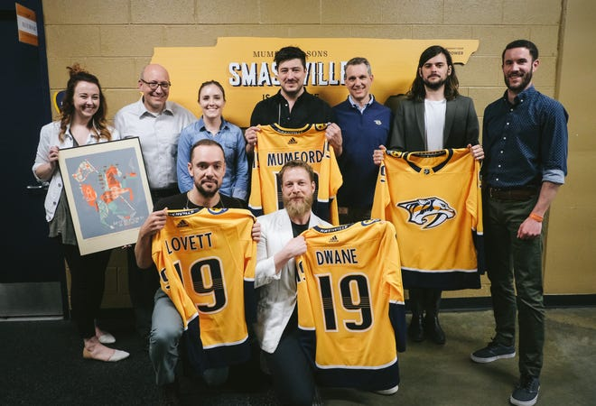 Mumford & Sons celebrated their record-breaking show at Bridgestone Arena with their own personalized Nashville Predators jerseys.