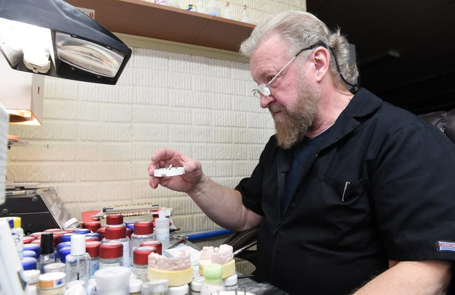 Lance Yates, owner of Prism Ceramics, applies porcelain to a custom dental implant abutment. Yates, who has always enjoyed making things and working with his hands, moved from metal and woodworking to dental work.