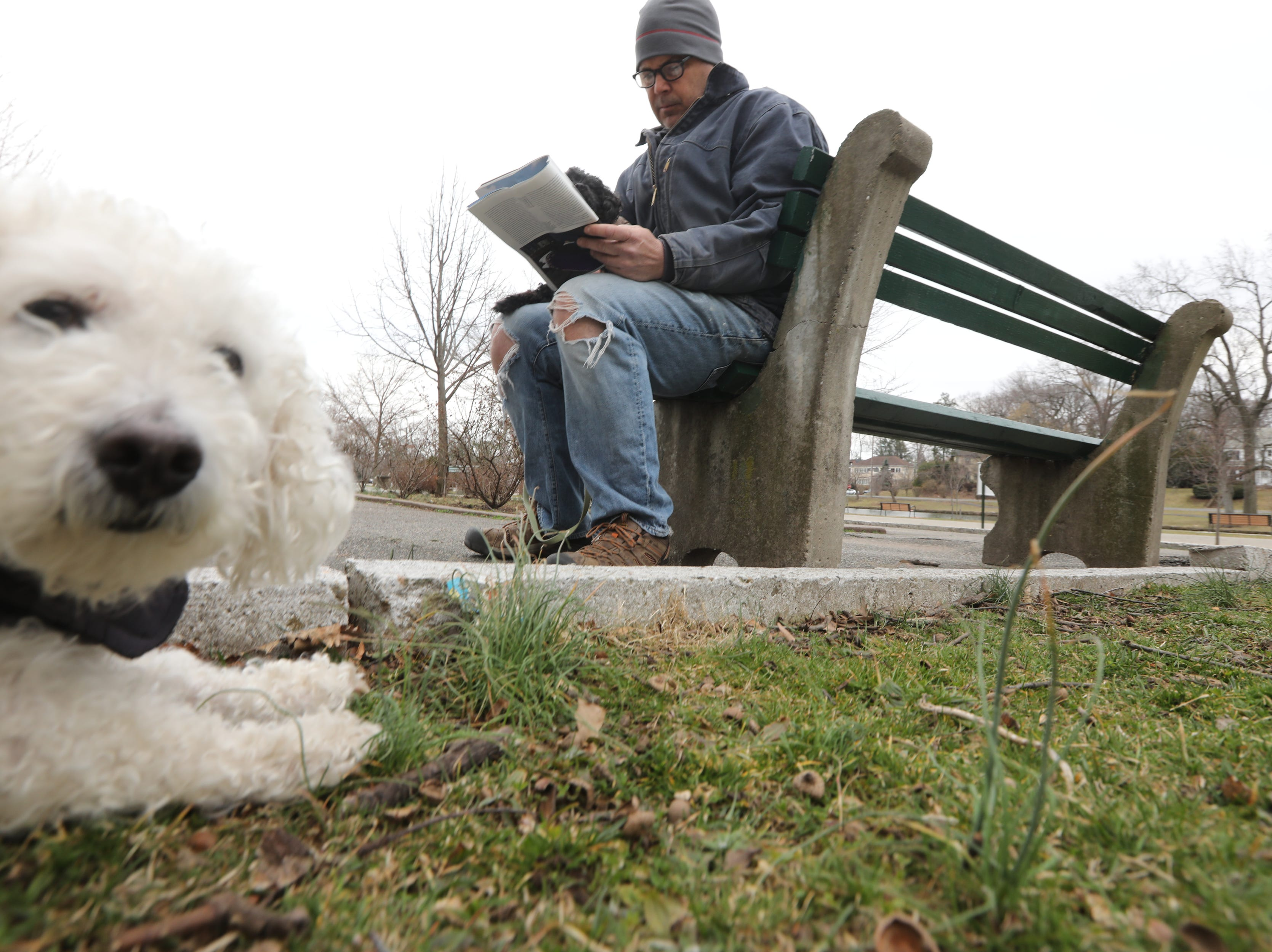 Fuzzy looks at the camera as Sasha sits on Darrell Taunt's lap as he reads at Third Ward Park, in Passaic. Monday, March 25, 2019
