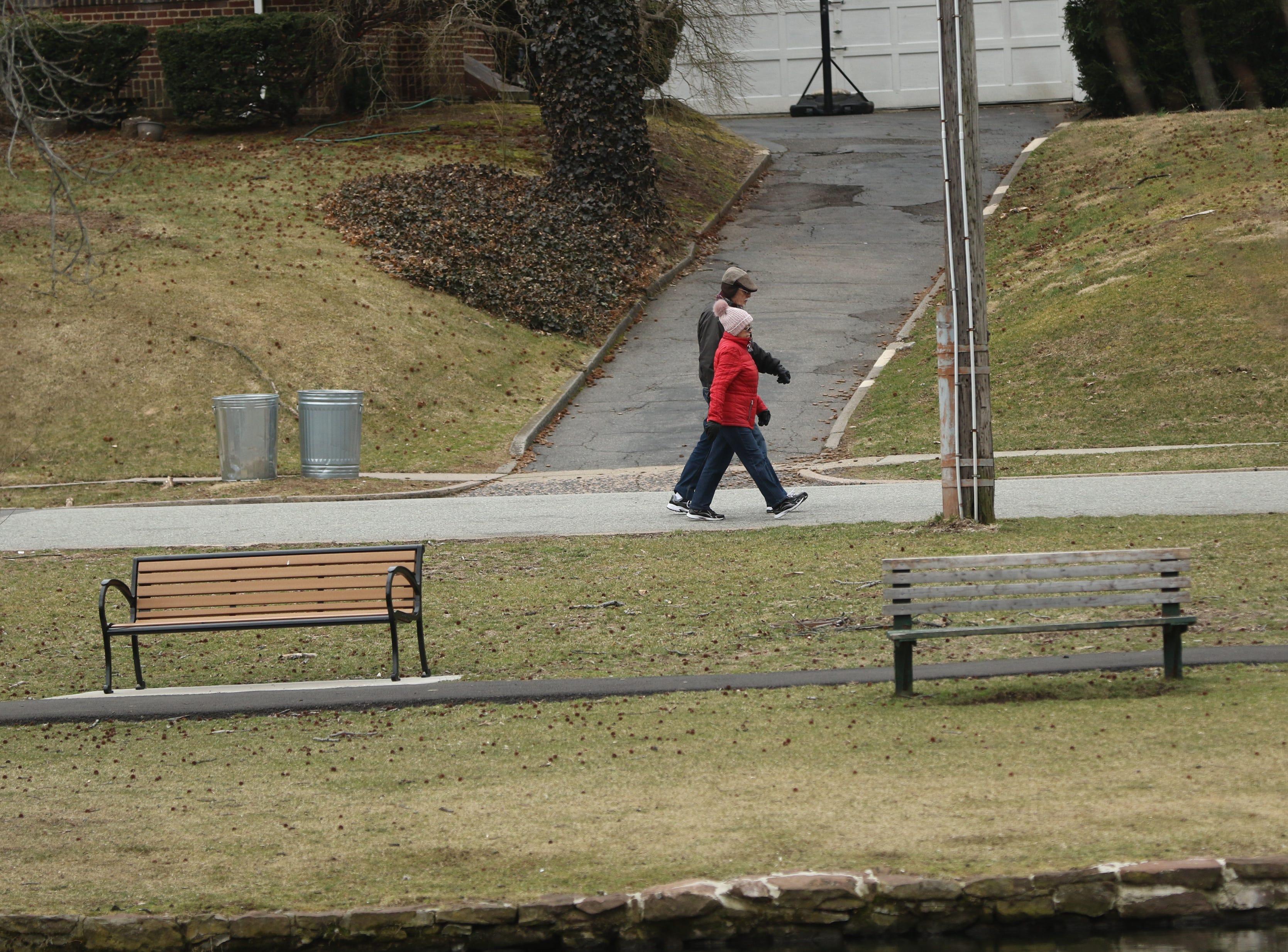 People walk around Third Ward Park, in Passaic, Monday, March 25, 2019.