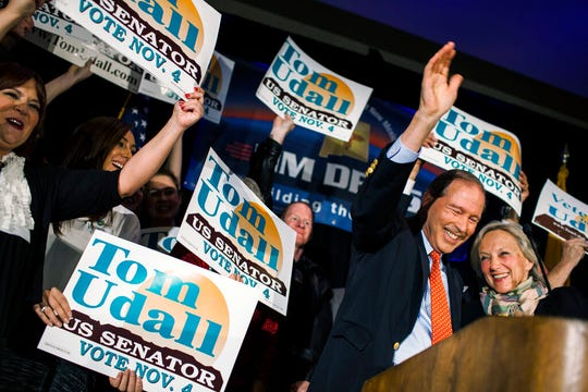 In this Nov. 4, 2014, file photo, Sen. Tom Udall, D-N.M., waves to supporters with his wife, Jill Cooper Udall, right, at the Double Tree hotel after being re-elected as one of New Mexico's Senators in Albuquerque, N.M. Udall says he will not seek re-election in 2020 in a move that opens up a secure Democratic seat to competition. He announced the end of his 20-year political career in Washington in a statement on Monday, March 25, 2019.