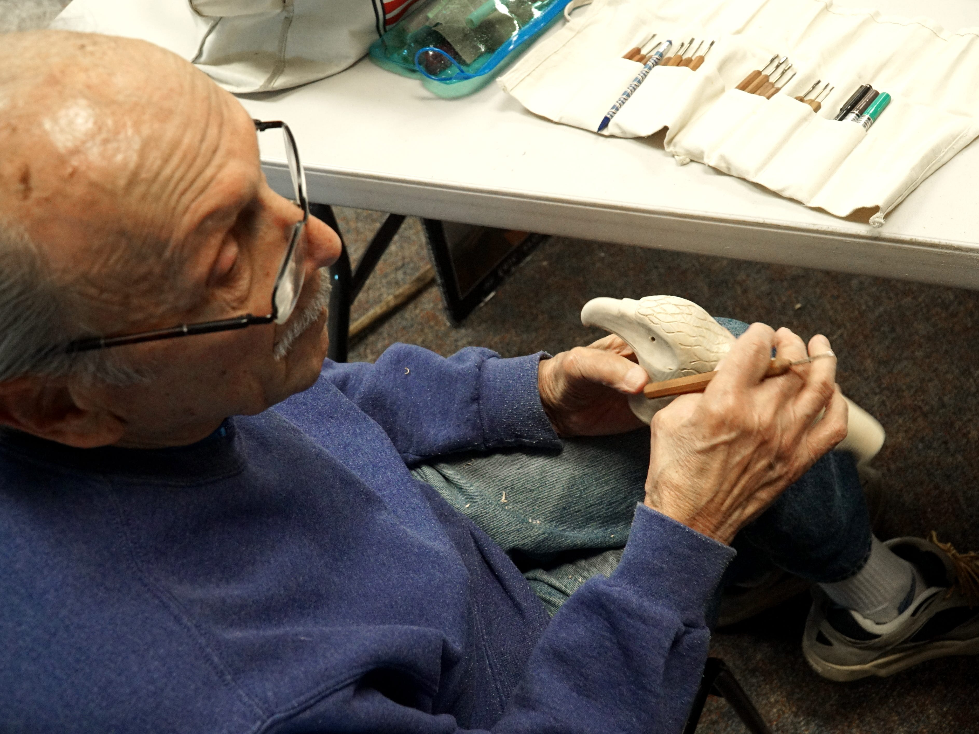 John Bluga pauses as he works on an eagle head cane for the Lean on Me veterans.