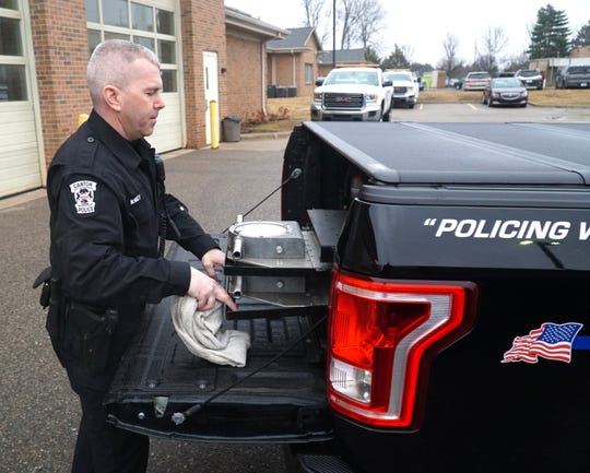 Canton Police Officer Alex McNulty pulls out the portable semi-truck weight scale that the department's Ford F-150 has stored in its bed. With it the officer can accurately measure the weight of a truck along the side of the highway.