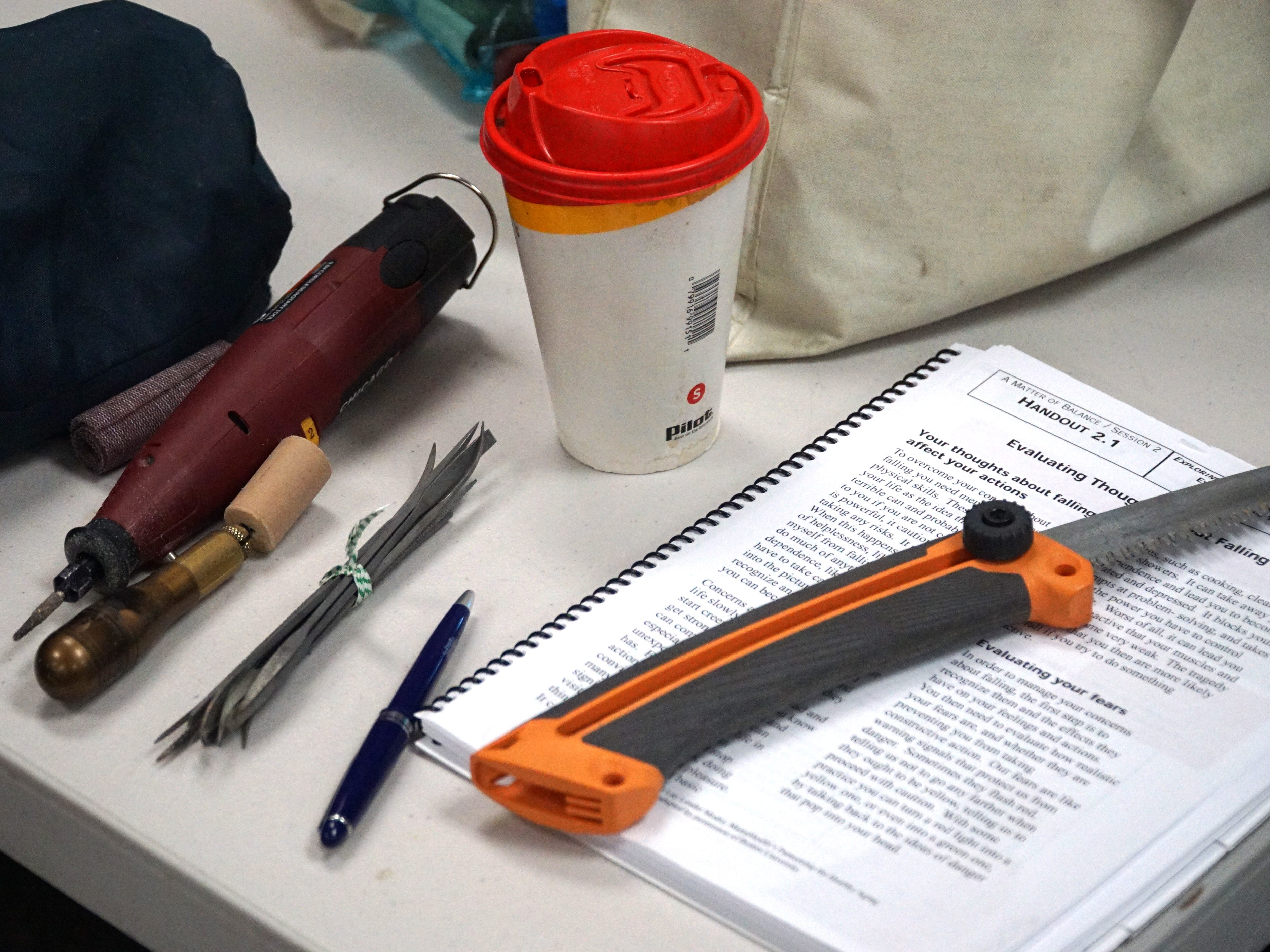 Some of the tools of the woodcarving trade: Exacto blades, small wood-carving points, a serated blade, Dremel tool and coffee.