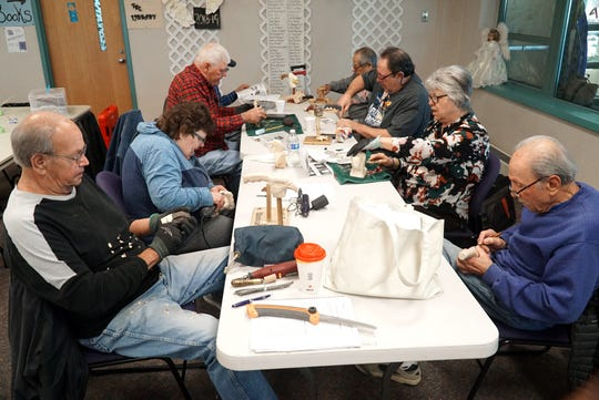 The Woodcarving Club takes up one table at the Center for Active Adults on March 25. Members bring their own power tools, cutting blades and blocks of wood to work on.