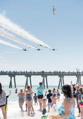 Hundreds of people crowd the beach to get a glimpse of the Blue Angels as they fly over Pensacola Beach on Monday, March 25, 2019.  The Blue Angels are coming home from winter training in El Centro, California.