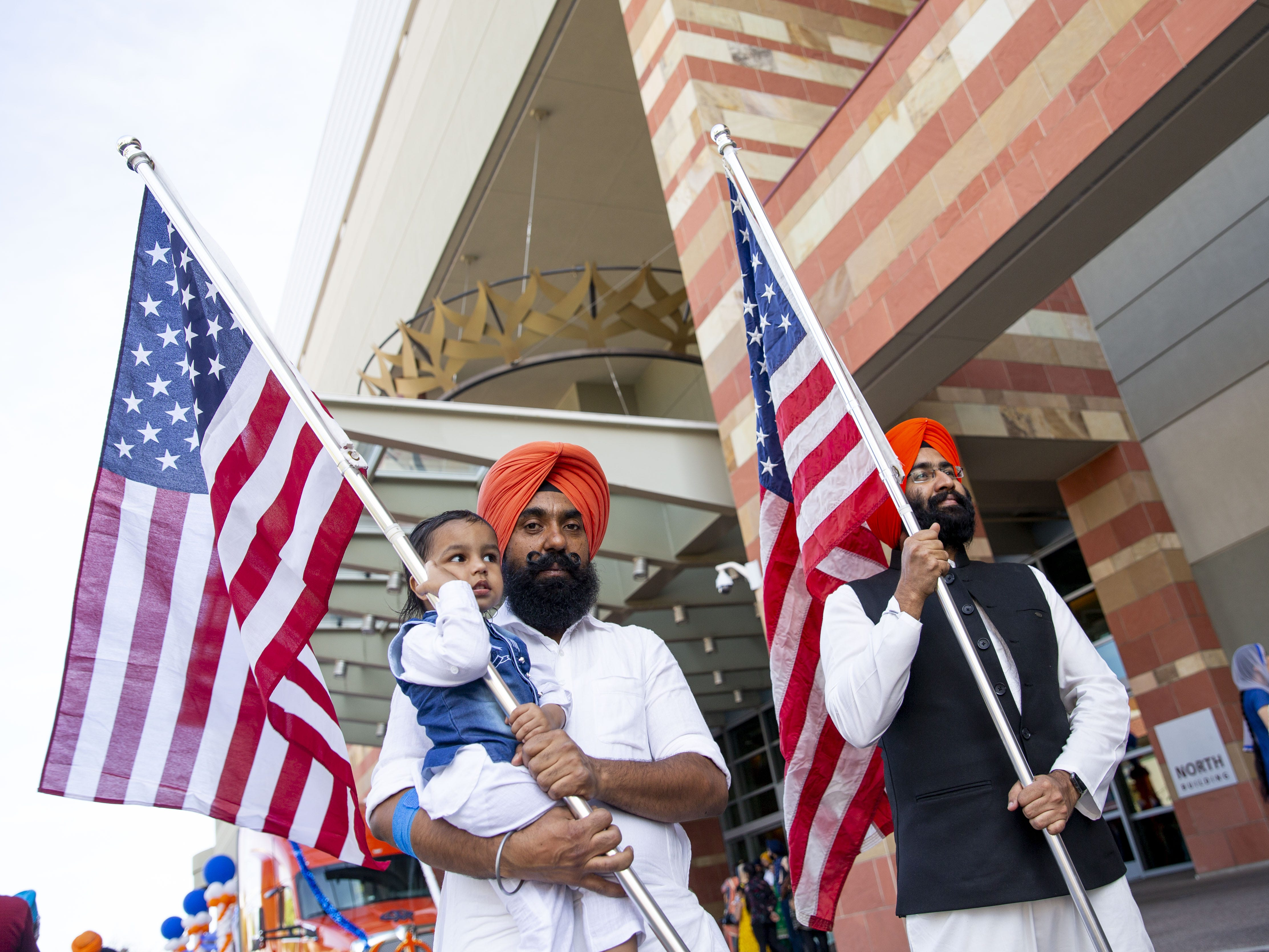 From left, Amtej Singh, 2, his father Satnam Singh, and Manmeet Singh pose with American flags before the Sikh parade begins in Phoenix on March 24, 2019.