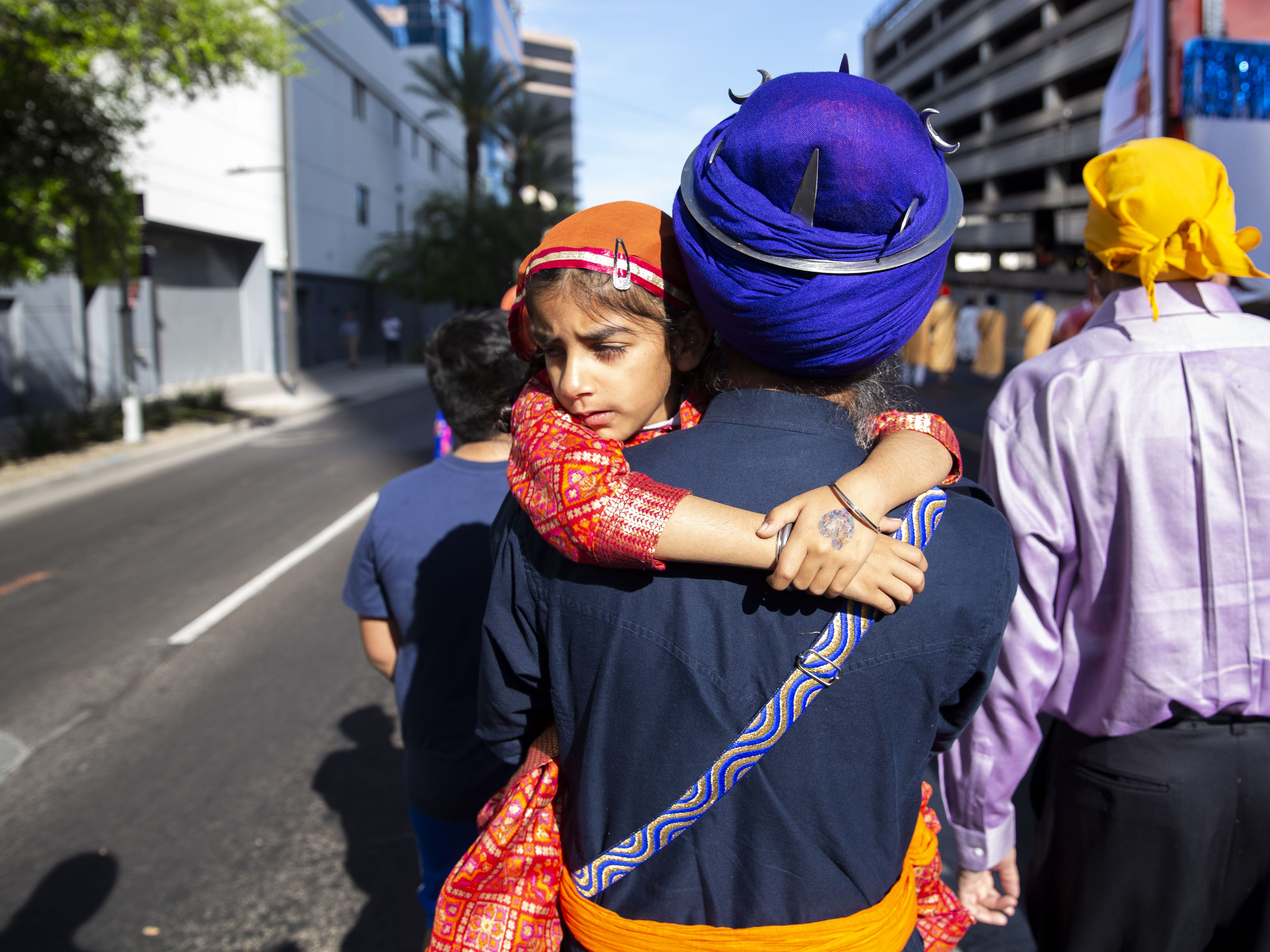 Raman Kaur, 6, clings to her father as he walks with a Nagar Kirtan procession through downtown Phoenix on March 24, 2019.