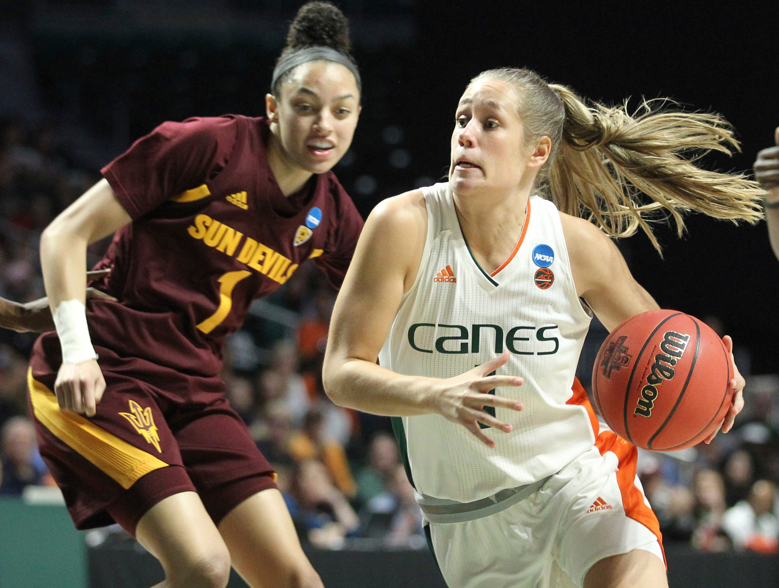 Miami's Laura Cornelius, center, moves the ball past Arizona State's Reili Richardson (1) during a second-round women's college basketball game in the NCAA Tournament, Sunday, March 24, 2019, in Coral Gables, Fla. (AP Photo/Luis M. Alvarez)