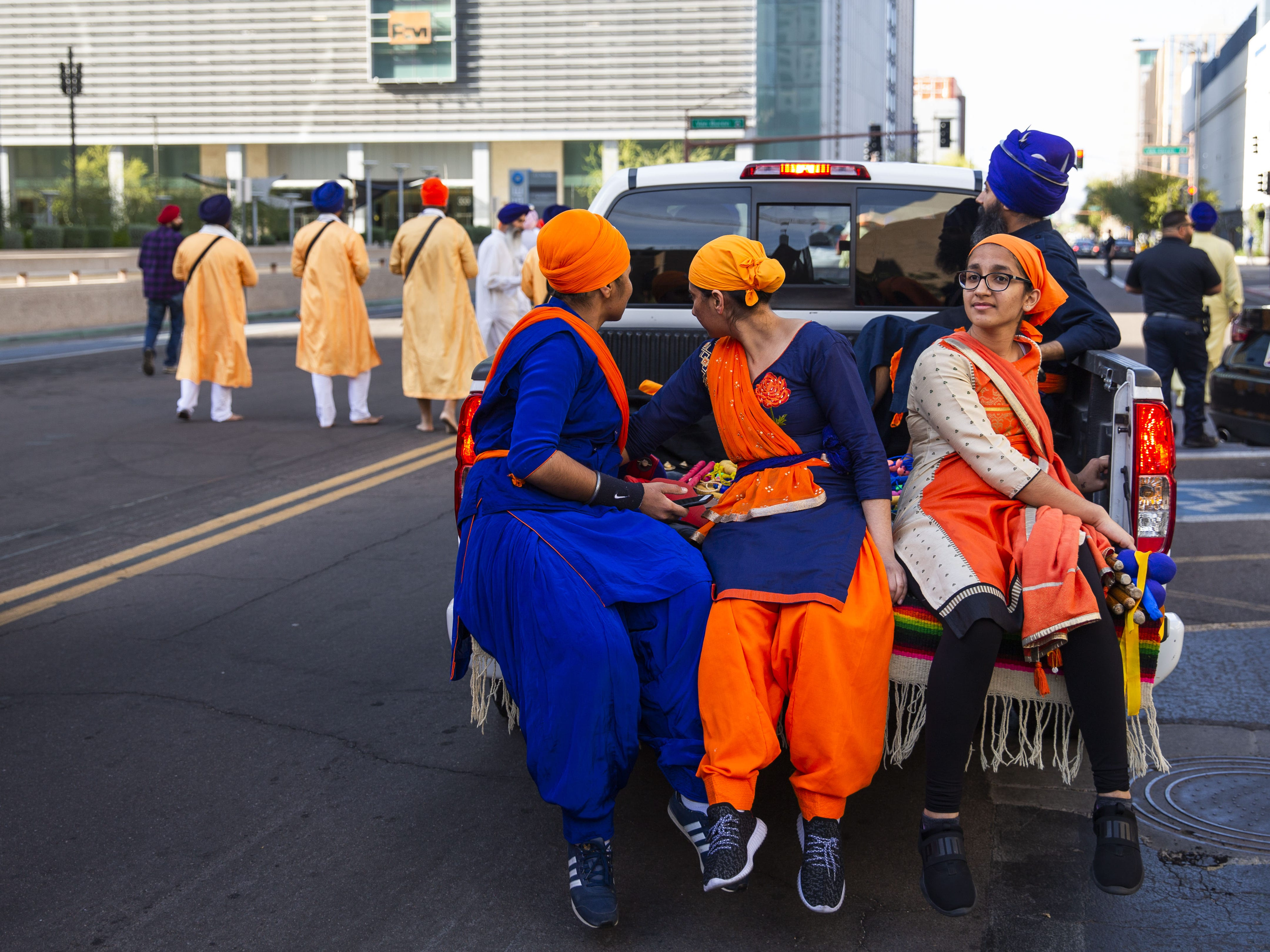 From left, Rupinder Kaur, Jasprit Kaur and Ashmin Kaur ride in the back of a pick-up truck with the Nagar Kirtan procession through downtown Phoenix on March 24, 2019.