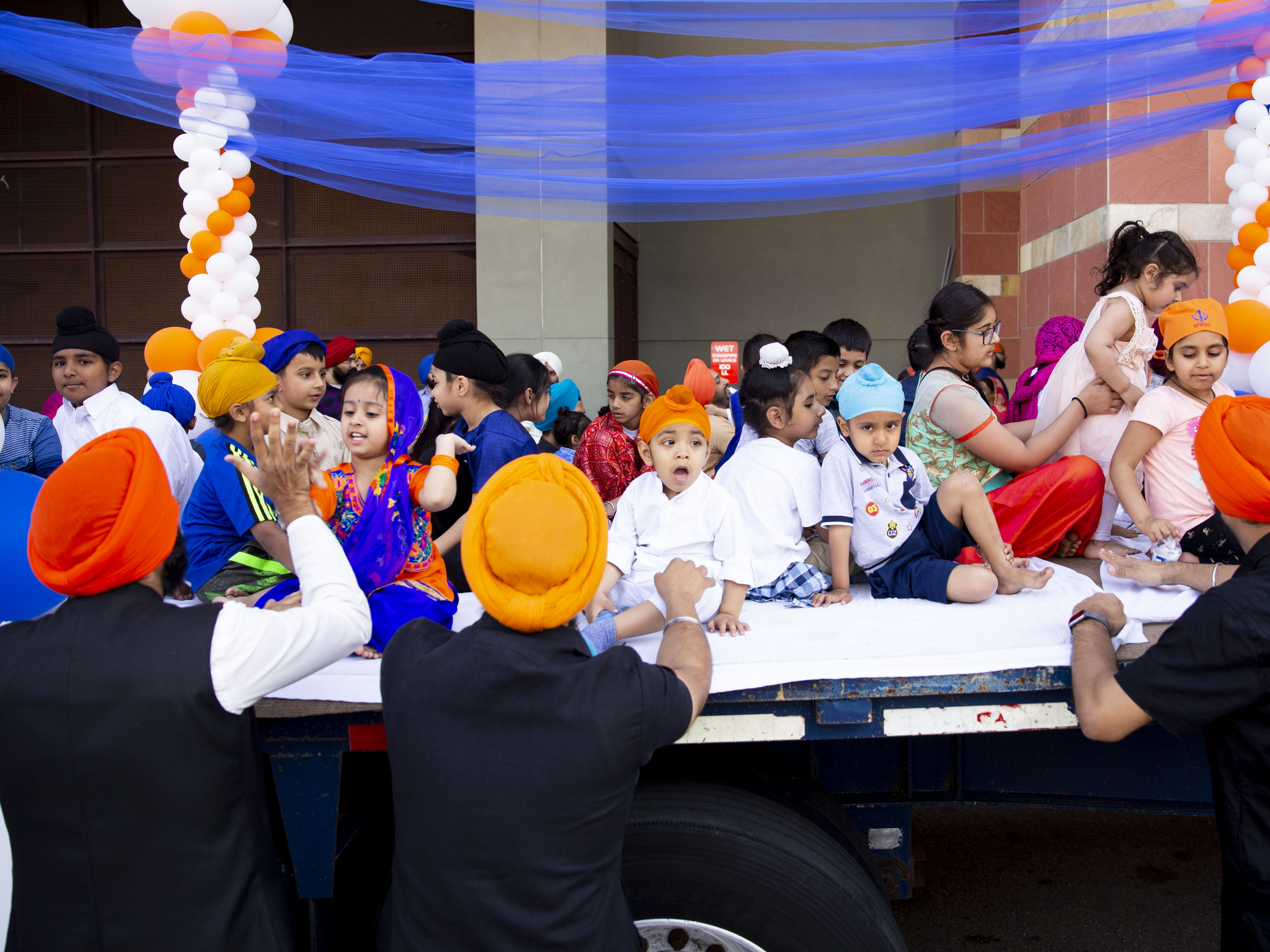 Parents put their children on a float for Nagar Kirtan, a Sikh parade, before it makes its way through the streets of downtown Phoenix on March 24, 2019.