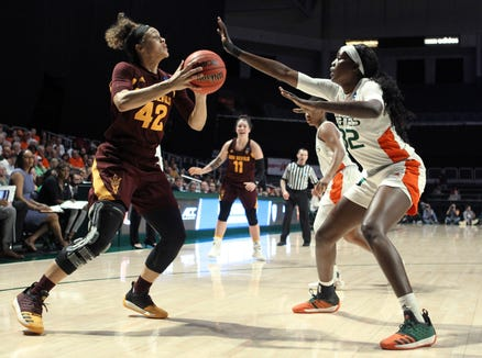 Arizona State's Kianna Ibis (42) moves the ball as Miami's Beatrice Mompremier, right, defends during a second-round women's college basketball game in the NCAA Tournament, Sunday, March 24, 2019, in Coral Gables, Fla. (AP Photo/Luis M. Alvarez)