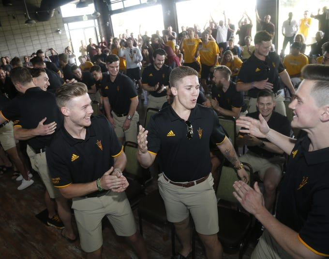 ASU's Joshua Maniscalco (R) high-fives teammate Brinson Pasichnuk (center) as they celebrate with Connor Stuart (2) during a NCAA Selection Show watch party at Papago Golf Course in Phoenix, Ariz. on March 24, 2019.