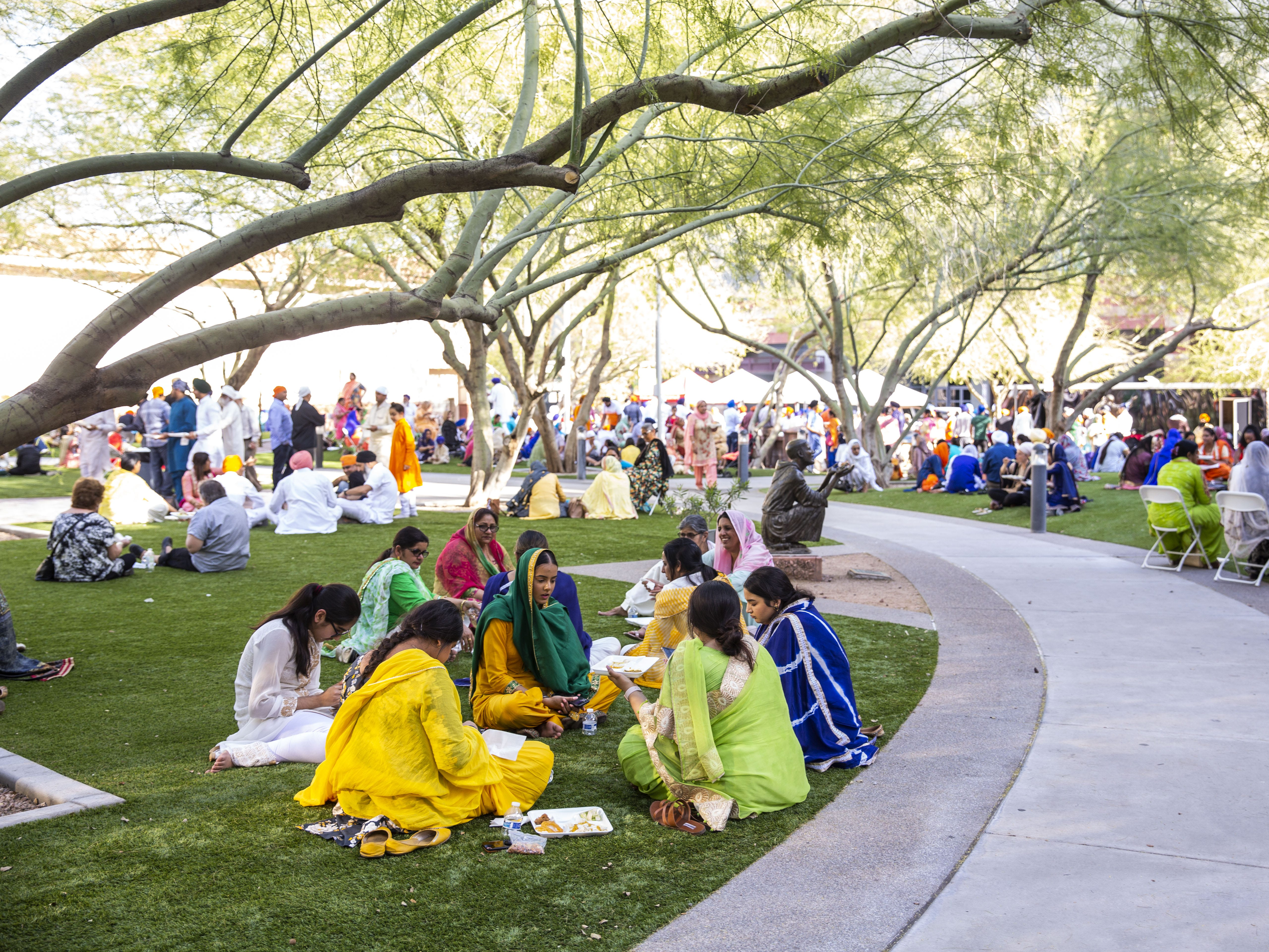 Families sit down by the Phoenix Convention Center and eat traditional food to celebrate Sikh traditions on March 24, 2019.